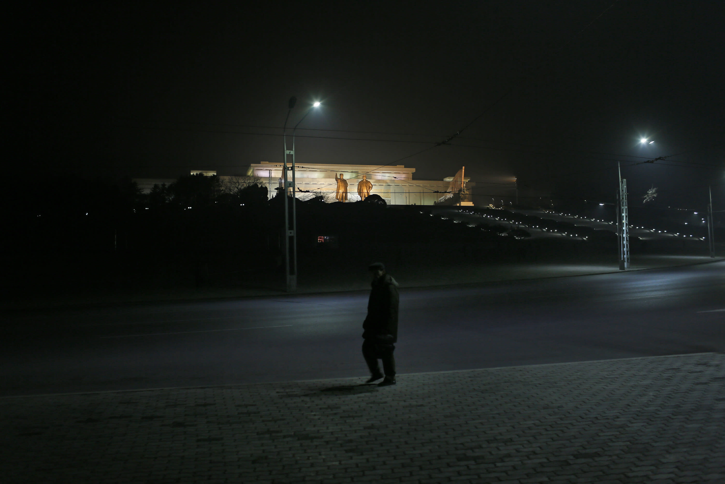 In this Tuesday Feb. 25, 2014 photo, a North Korean man walks on a street against the statues of the late leaders Kim Il Sung and Kim Jong Il at Mansu Hill in Pyongyang, North Korea. (AP Photo/Vincent Yu)