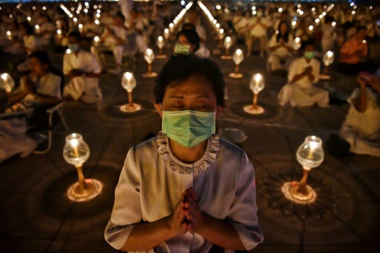 Buddhist worshippers wearing protective masks attend prayers at Wat Dhammakaya Buddhist temple in Bangkok -- Thailand has announced 14 confirmed coronavirus infections (AFP Photo/Lillian SUWANRUMPHA)