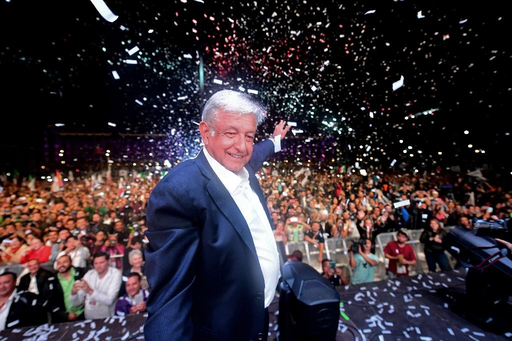Mexico's president-elect Andres Manuel Lopez Obrador (C) cheers his supporters at the Zocalo Square in Mexico City after winning general elections (AFP Photo/PEDRO PARDO)