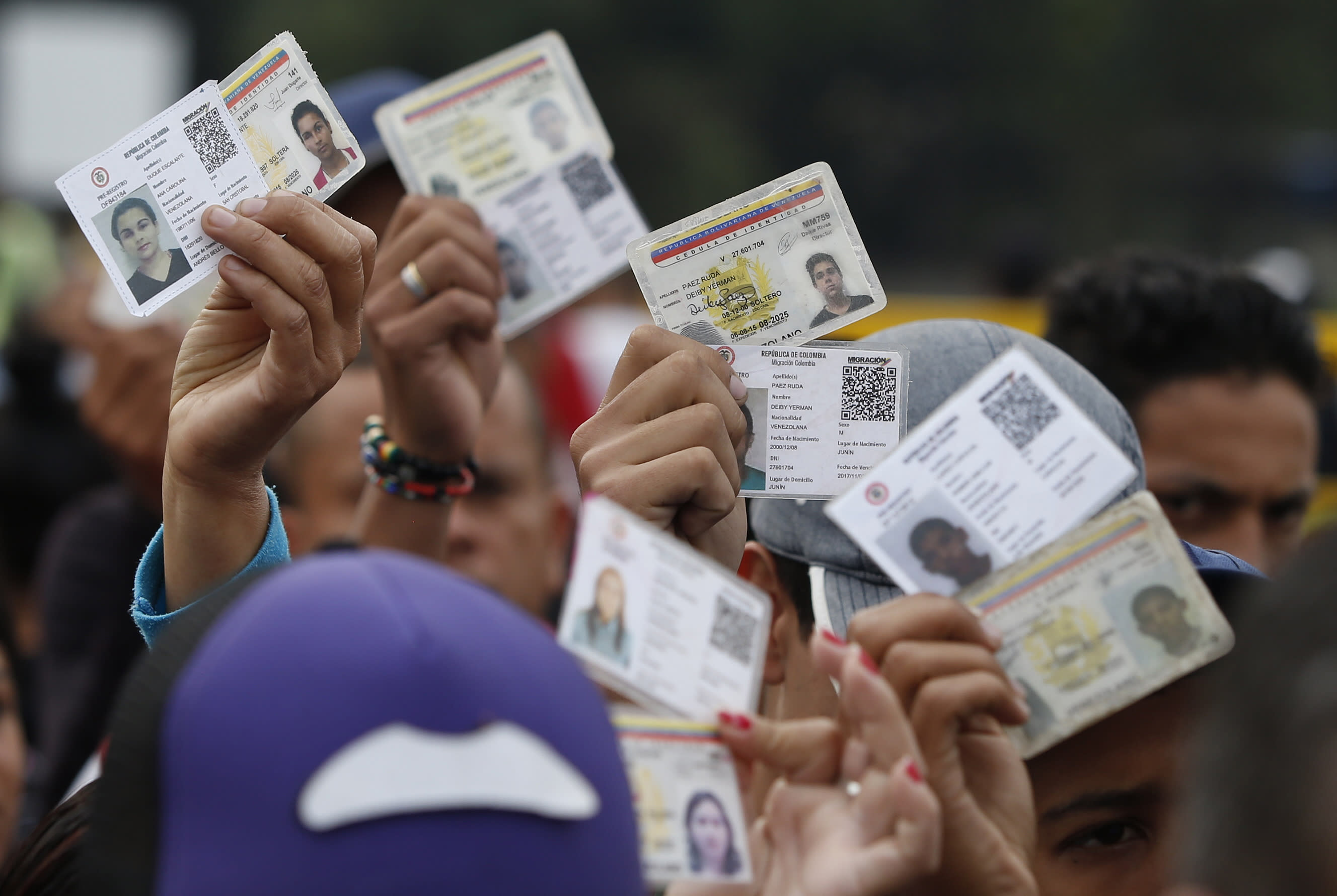 <p>Venezuelan citizens hold up their identification cards for inspection by the Colombian immigration police, in Cucuta, Colombia, on the border with Venezuela on Feb. 22, 2018. (Photo: Fernando Vergara/AP) </p>