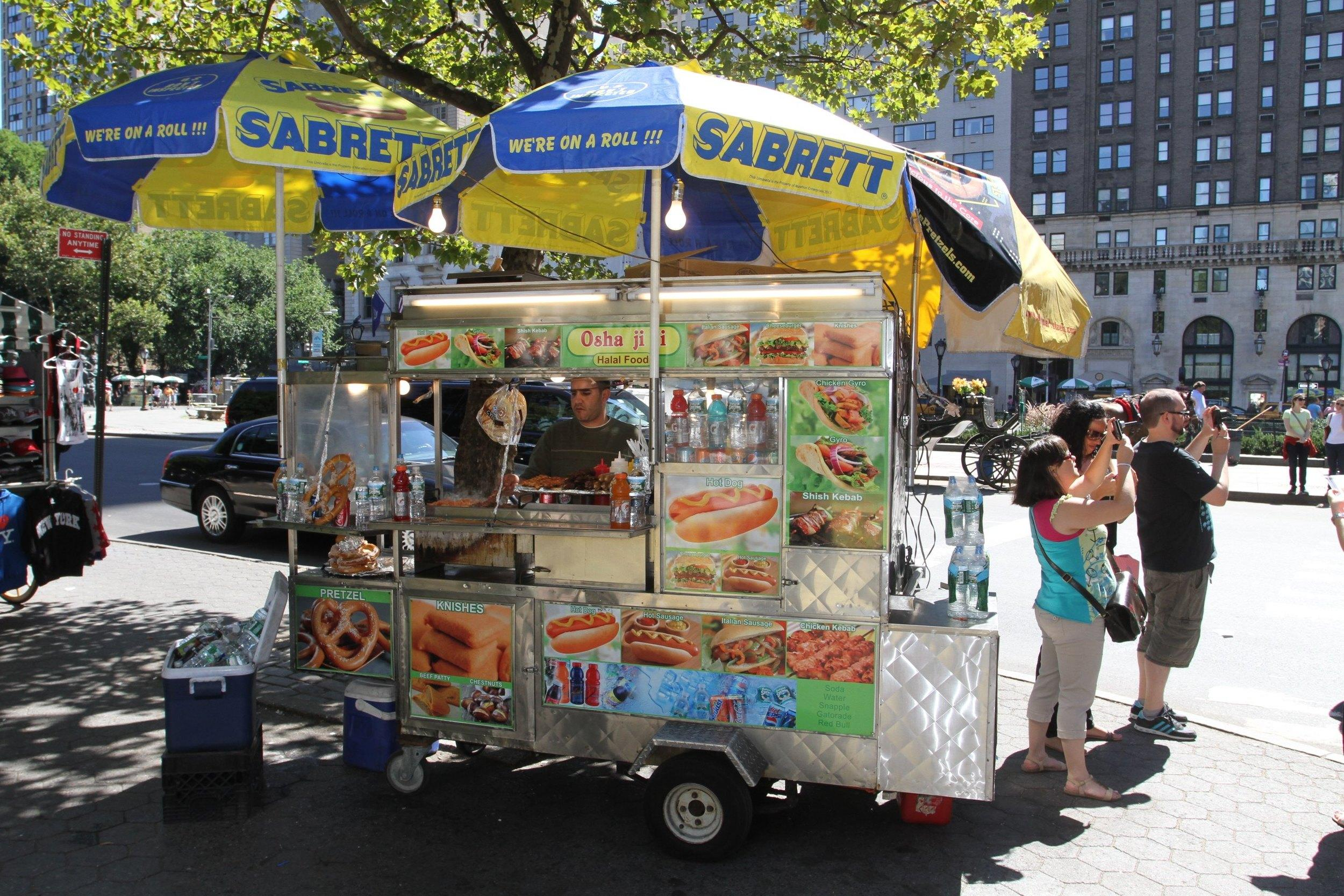 NEW YORK - AUGUST 24:  A street vendor selling food on August 24, 2013 on Fifth Avenue in New York City.  (Photo by Waring Abbott/Getty Images)