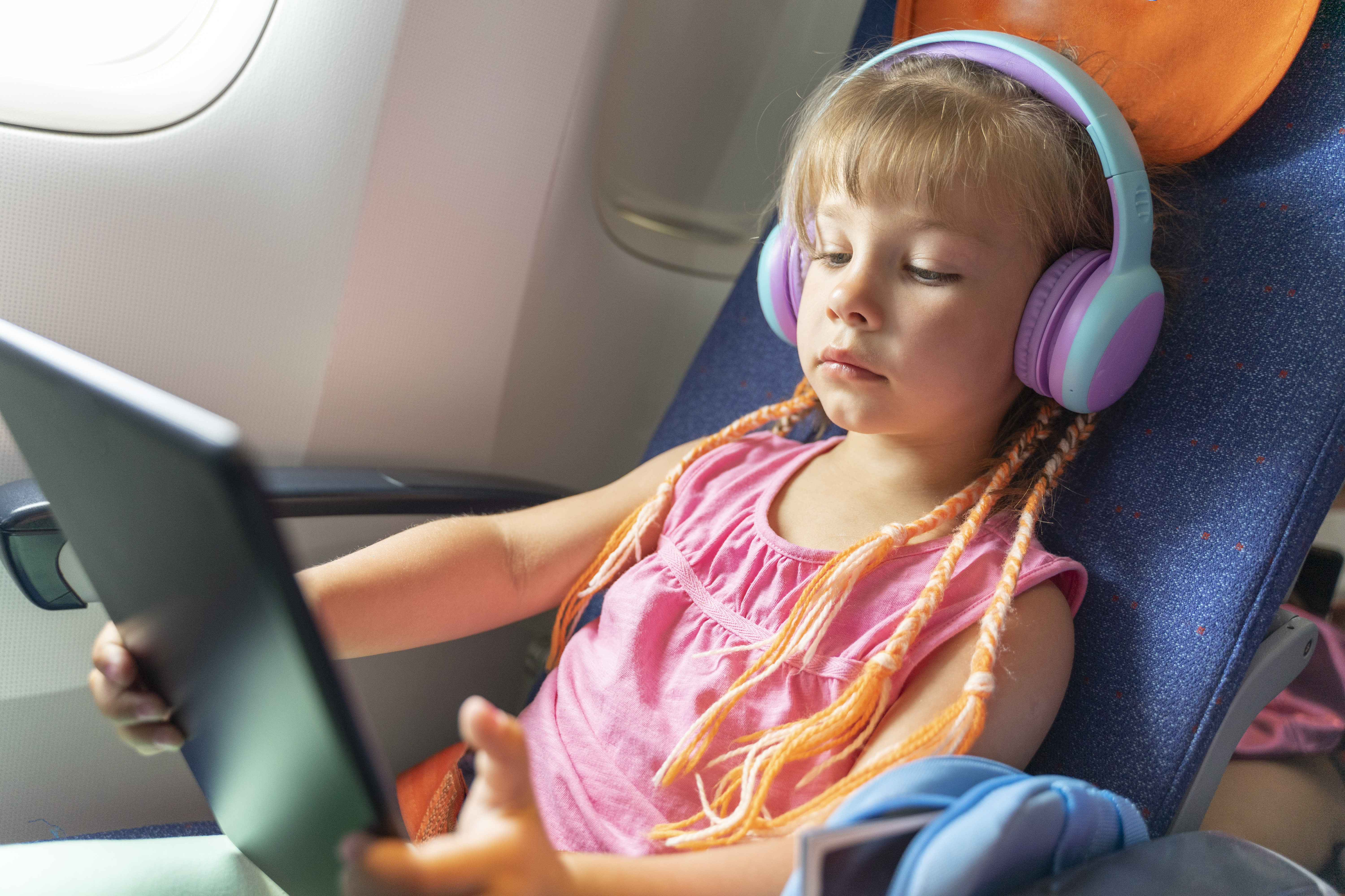 Caucasian girl with headphones watching and listening in flight entertainment on board an airplane