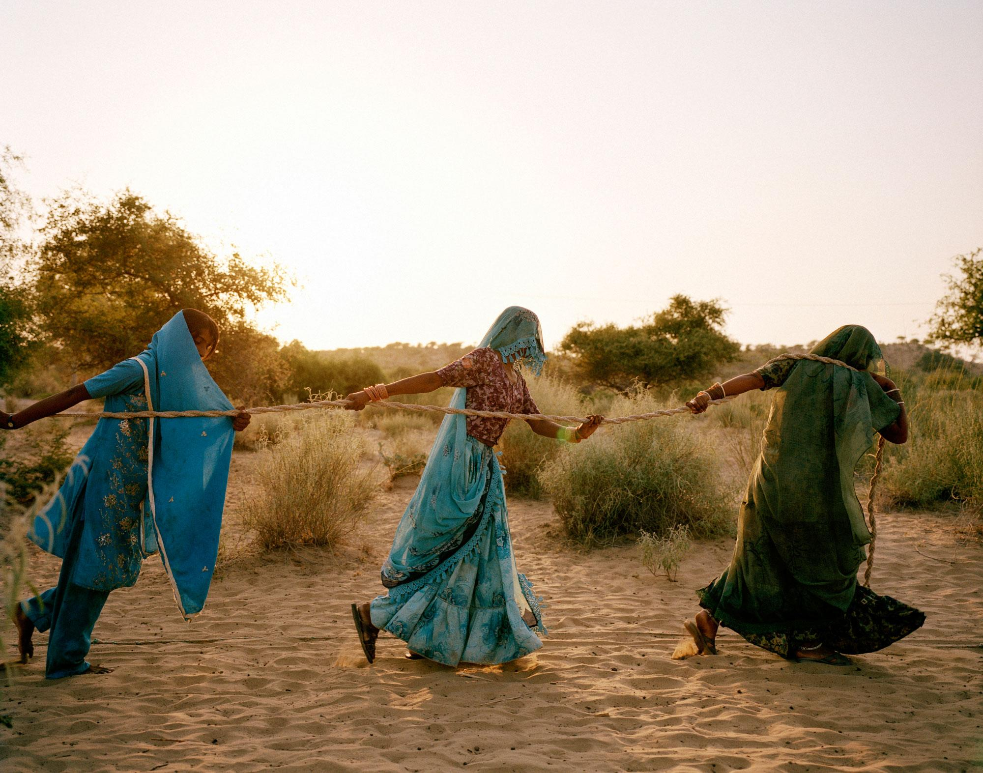 "<p>Women haul water from a 150-foot-deep well in the Thar desert, three hours' walk from their home in Bewatoo, Tharparkar, Sindh, Pakistan, 2013. Temperatures there hover at 48-50°C on summer days. With an extremely low water table and continuing drought, sometimes water must be hauled from a depth of 150 to 200 feet. ""Women fall unconscious on their way to these dug wells,"" says Marvi Bheel, 45, a resident of Bewatoo, Tharparkar. From the water-scarce regions in southern Ethiopia to the desert wells of Pakistan, it is women who are primarily responsible for gathering water. (Photograph by Mustafah Abdulaziz/WaterAid) </p>"
