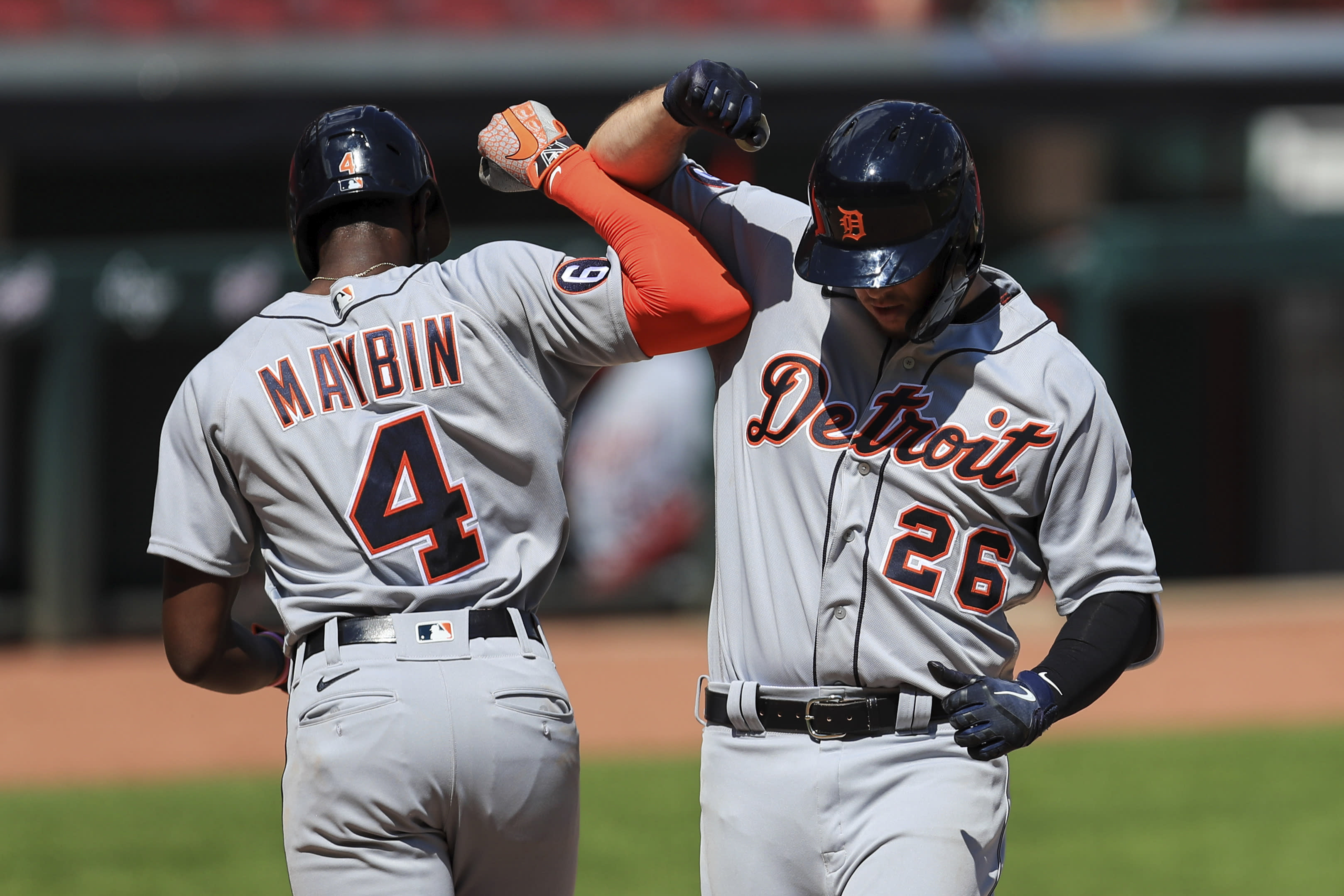 Detroit Tigers' C.J. Cron (26) celebrates with Cameron Maybin (4) after hitting a two-run home run in the ninth inning during a baseball game against the Detroit Tigers at Great American Ballpark in Cincinnati, Sunday, July 26, 2020. (AP Photo/Aaron Doster)