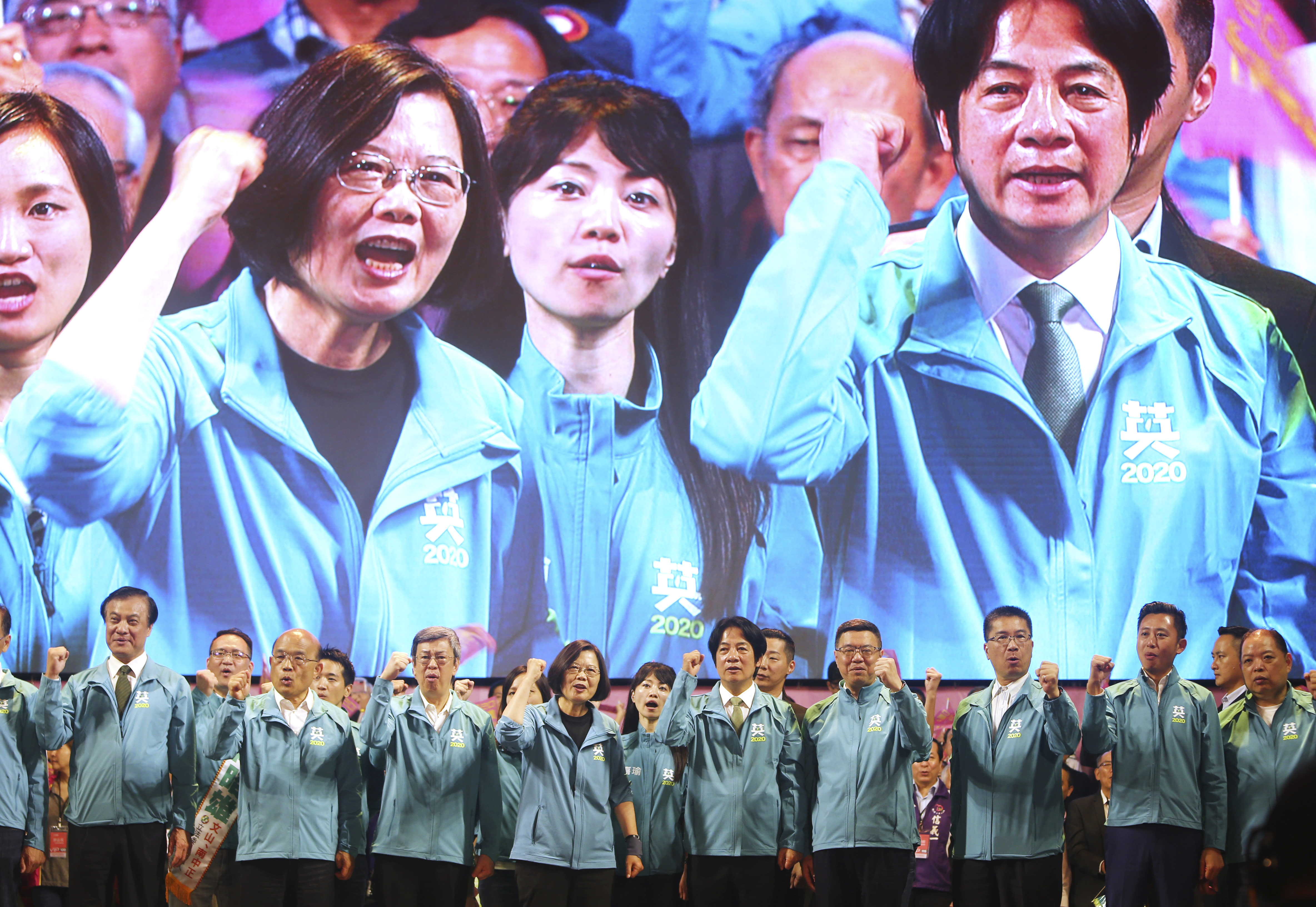 Taiwan President and Democratic Progressive Party presidential candidate Tsai Ing-wen, front fourth from left, and her running mate William Lai, fifth left, are seen on screen above as Tsai launches her re-election campaign in Taipei, Taiwan, Sunday, Nov. 17, 2019. Taiwan will hold its presidential election on Jan. 11, 2020. (AP Photo/Chiang Ying-ying)