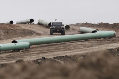 A vehicle drives next to a series of pipes at a Dakota Access Construction site near the town of Cannon Ball, North Dakota, U.S., October 30, 2016. REUTERS/Josh Morgan