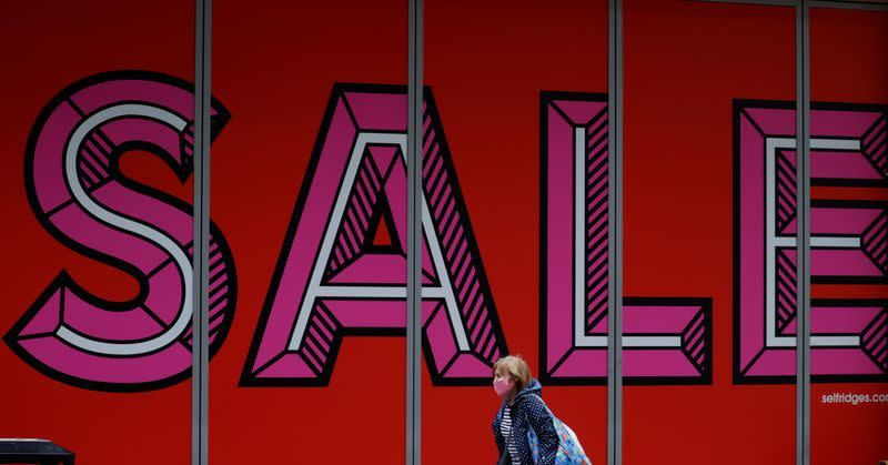 A woman wearing a protective face covering walks past a sale sign in a shop window following the outbreak of the coronavirus disease (COVID-19), in Manchester, Britain