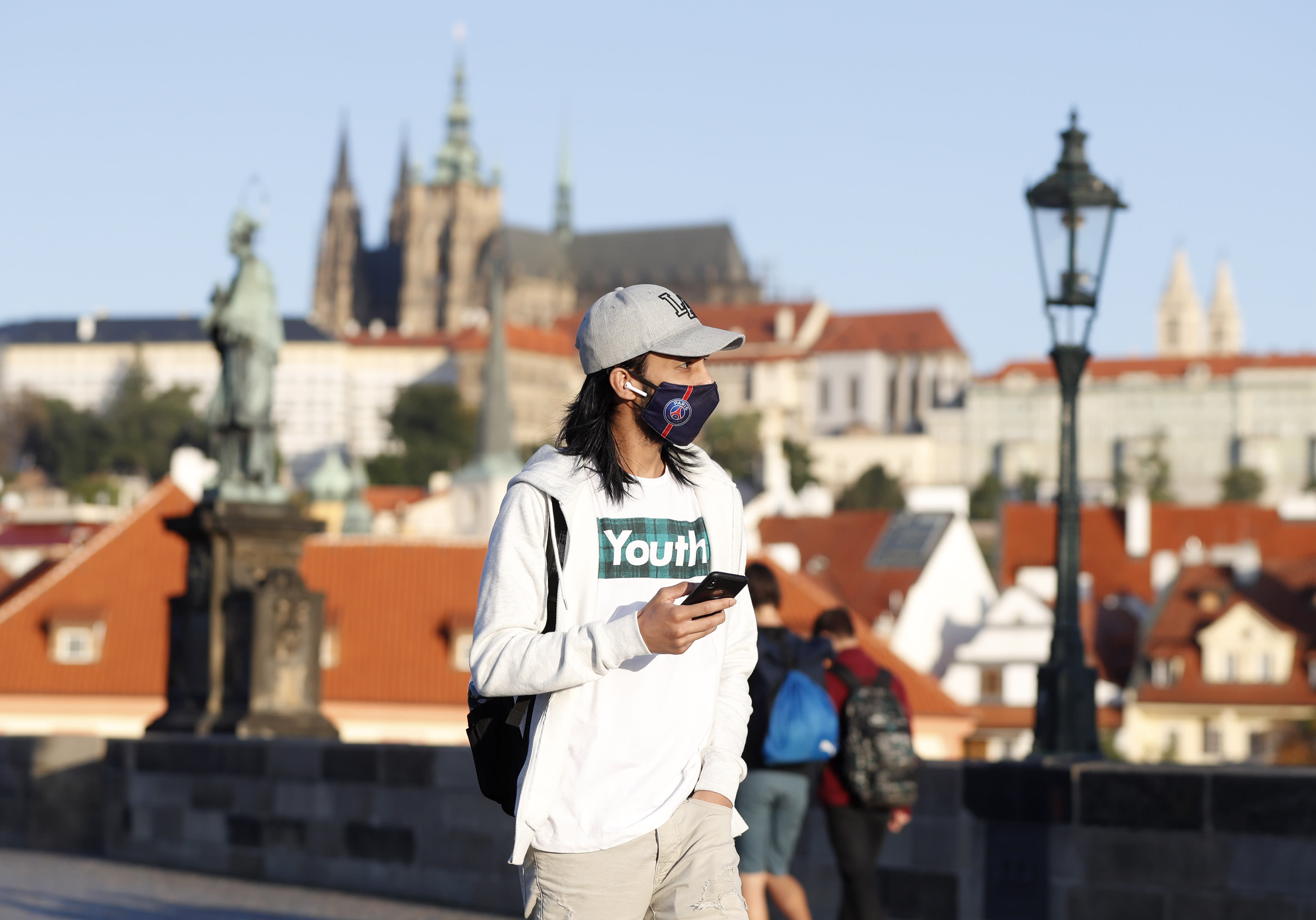 A young man wearing a face mask walks across the medieval Charles Bridge in Prague, Czech Republic, Friday, Sept. 18, 2020. The Czech Republic has been been facing the second wave of infections. The number of new confirmed coronavirus infections has been setting new records almost on a daily basis, currently surpassing 3,000 cases in one day for the first time. (AP Photo/Petr David Josek)