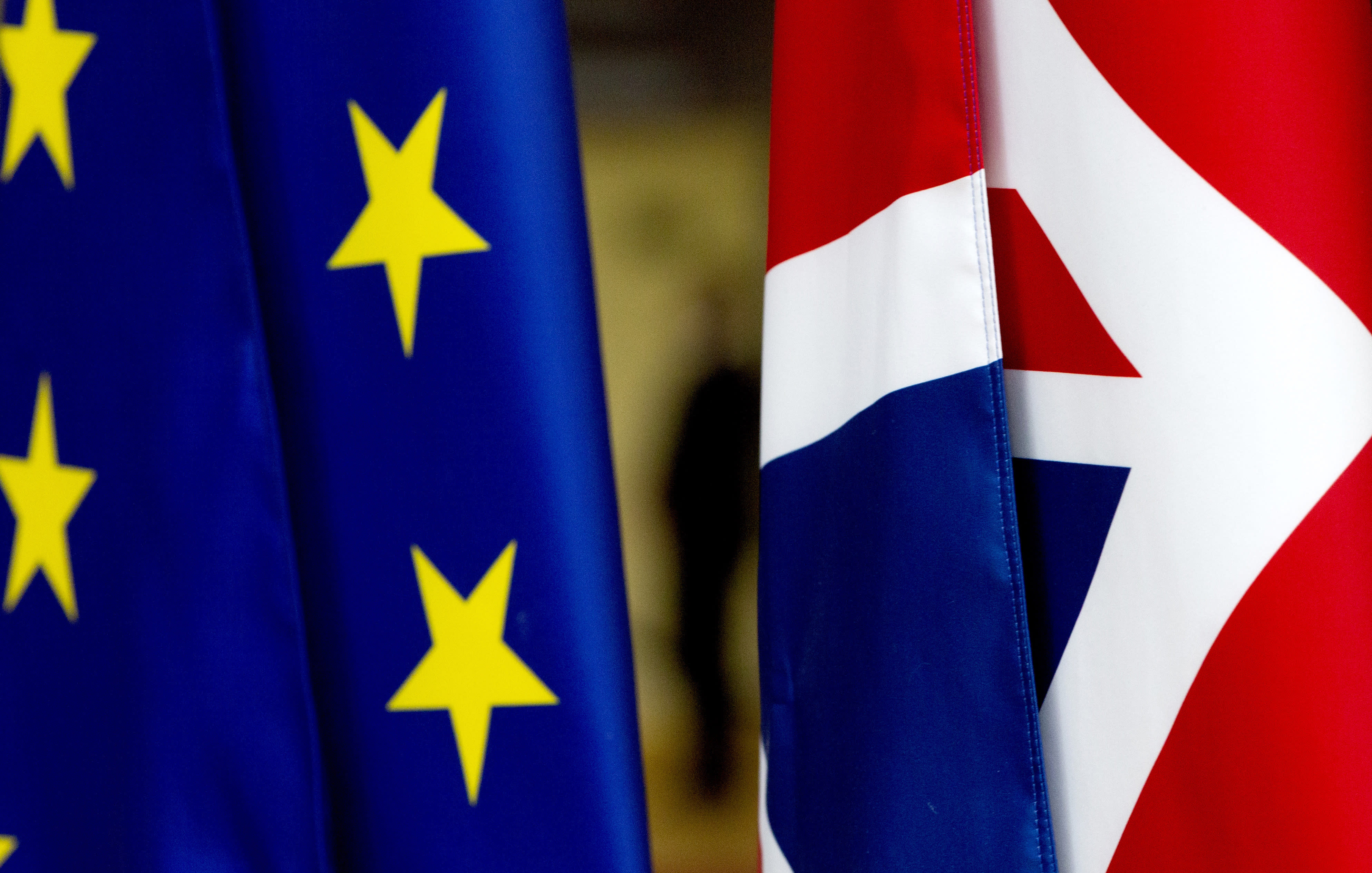 F|ILE - In this file photo dated Tuesday, Jan. 28, 2020, the British Union flag, right, and the EU flag, seen inside the atrium at the Europa building in Brussels. The number of Britons moving to live in European Union countries has soared since the Brexit vote in 2016, a U.K.-German study has revealed Tuesday Aug. 4, 2020.(AP Photo/Virginia Mayo, FILE)