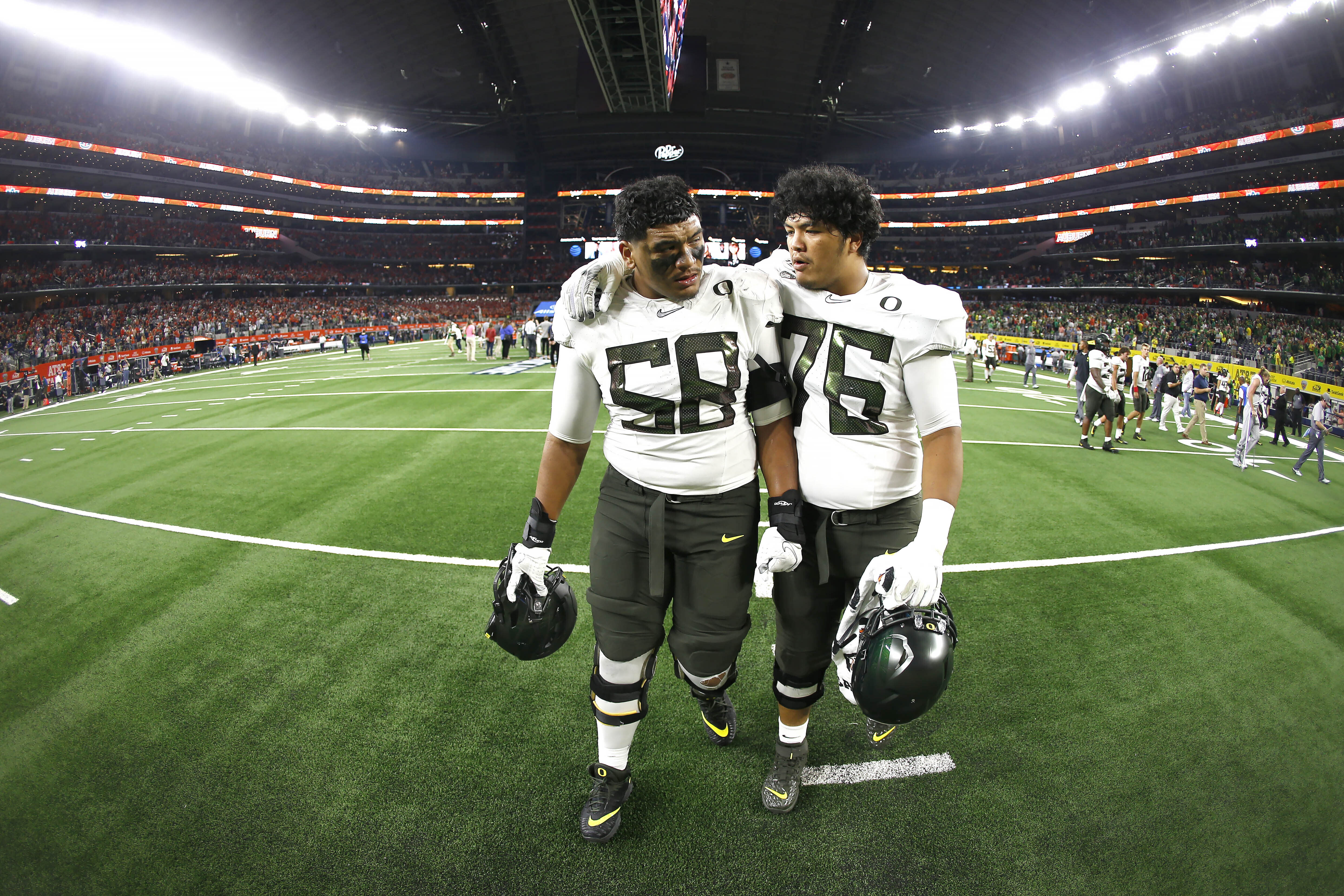 Oregon offensive linemen Penei Sewell (58) and Jonah Tauanu'u (76) walk off the field after the team's 27-21 loss to Auburn following an NCAA college football game, Saturday, Aug. 31, 2019, in Arlington, Texas. (AP Photo/Ron Jenkins)