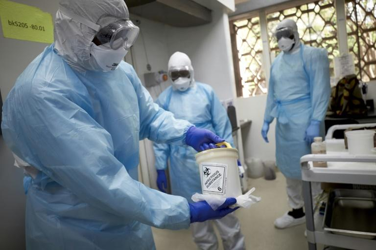 Mali, mired in an eight-year-old conflict, said two nationals who had returned from France tested positive for the virus. Here, a Malian researcher holds a sample to be tested at a research center in Bamako (AFP Photo/MICHELE CATTANI)