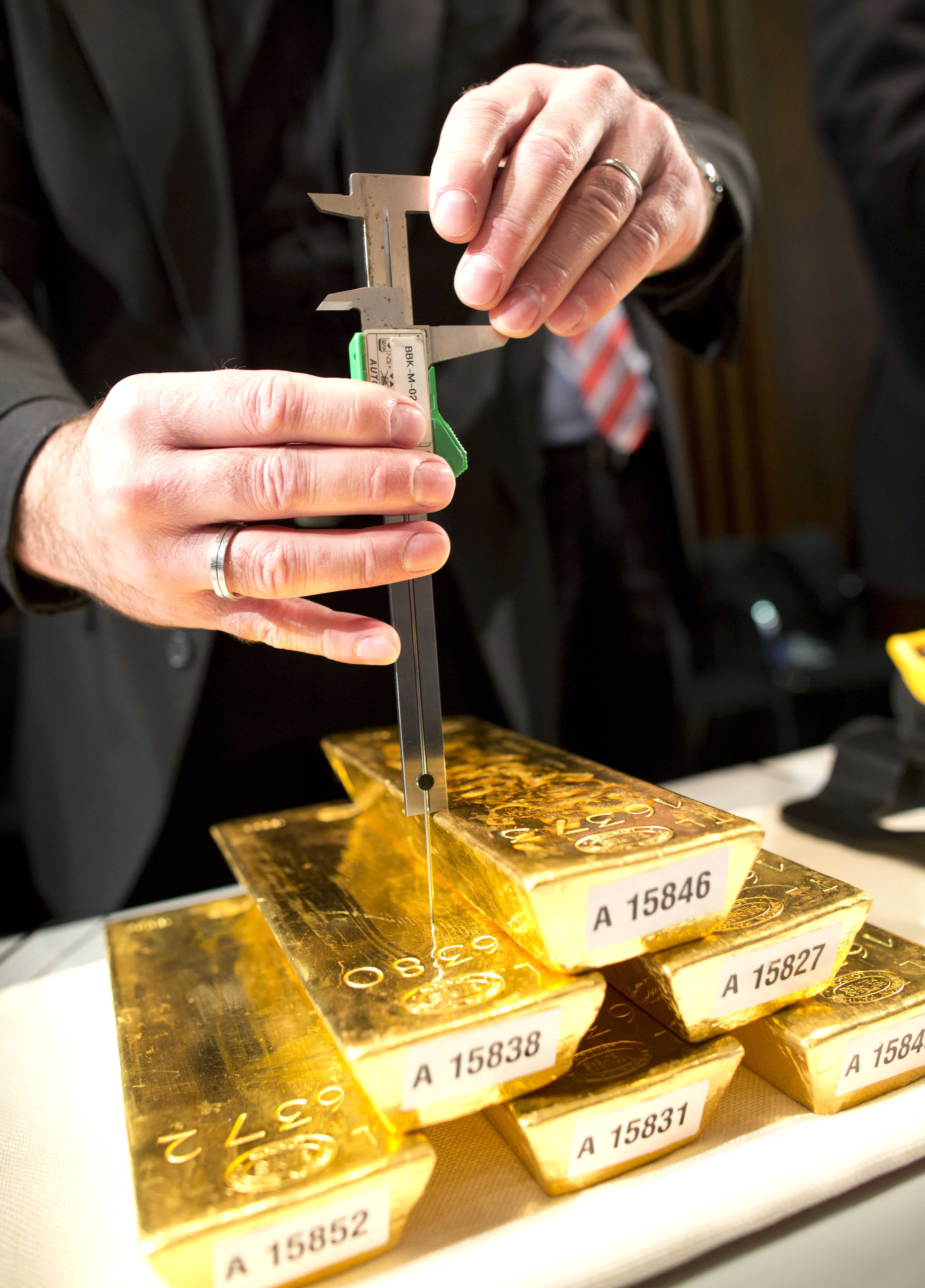 A bank employee meassures a gold ingot during a press conference at the German central bank in Frankfurt, Germany, Wednesday Jan. 16, 2013. Germany's central bank is to bring back home some US $36 billion ( 27 billion euro) worth of gold stored in the United States and France. The Bundesbank said in a statement Wednesday that it will repatriate all 374 tons of gold it had stored in Paris by 2020. An additional 300 tons - equivalent to 8 percent of the Bundesbank's total reserves worth about US$183 billion _ will also be shipped from New York to Frankfurt. Frankfurt will hold half of Germany's 3,400 tons of gold by 2020, with New York retaining 37 percent and London storing 13 percent. The move follows criticism from Germany's independent Federal Auditors' Office last year bemoaning the central bank's oversight of gold reserves abroad. (AP Photo/dpa/ Frank Rumpenhorst)