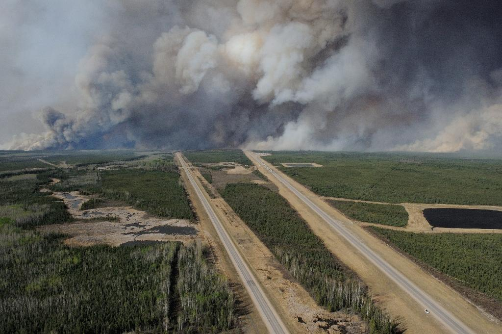 An aerial view of highway 63 as smoke from fires billows south of Fort McMurray, taken from a CH-146 Griffon helicopter (AFP Photo/MCpl VanPutten)