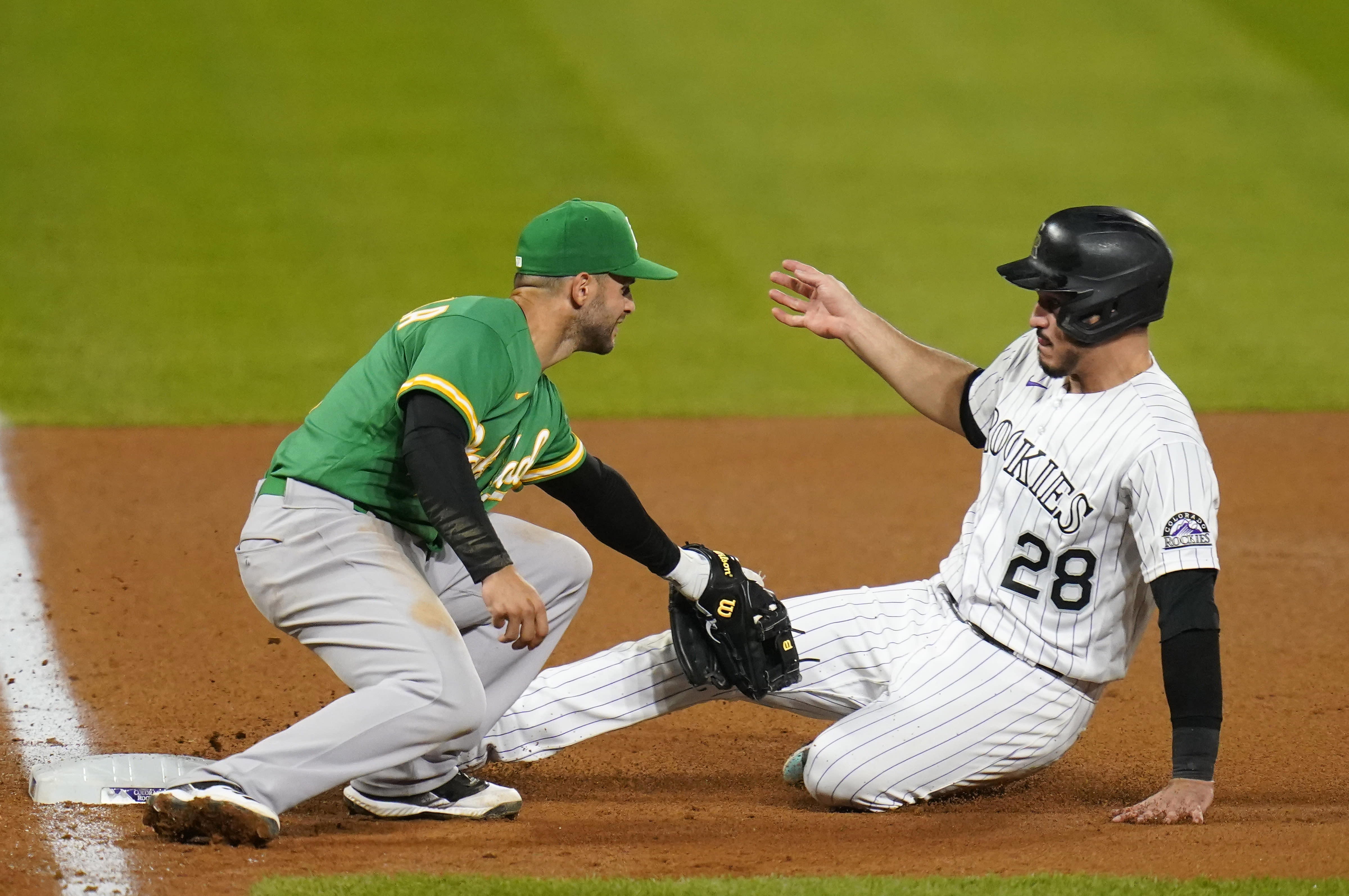 Oakland Athletics third baseman Tommy La Stella tags out Colorado Rockies' Nolan Arenado during the eighth inning of a baseball game, Tuesday, Sept. 15, 2020, in Denver. (AP Photo/Jack Dempsey)
