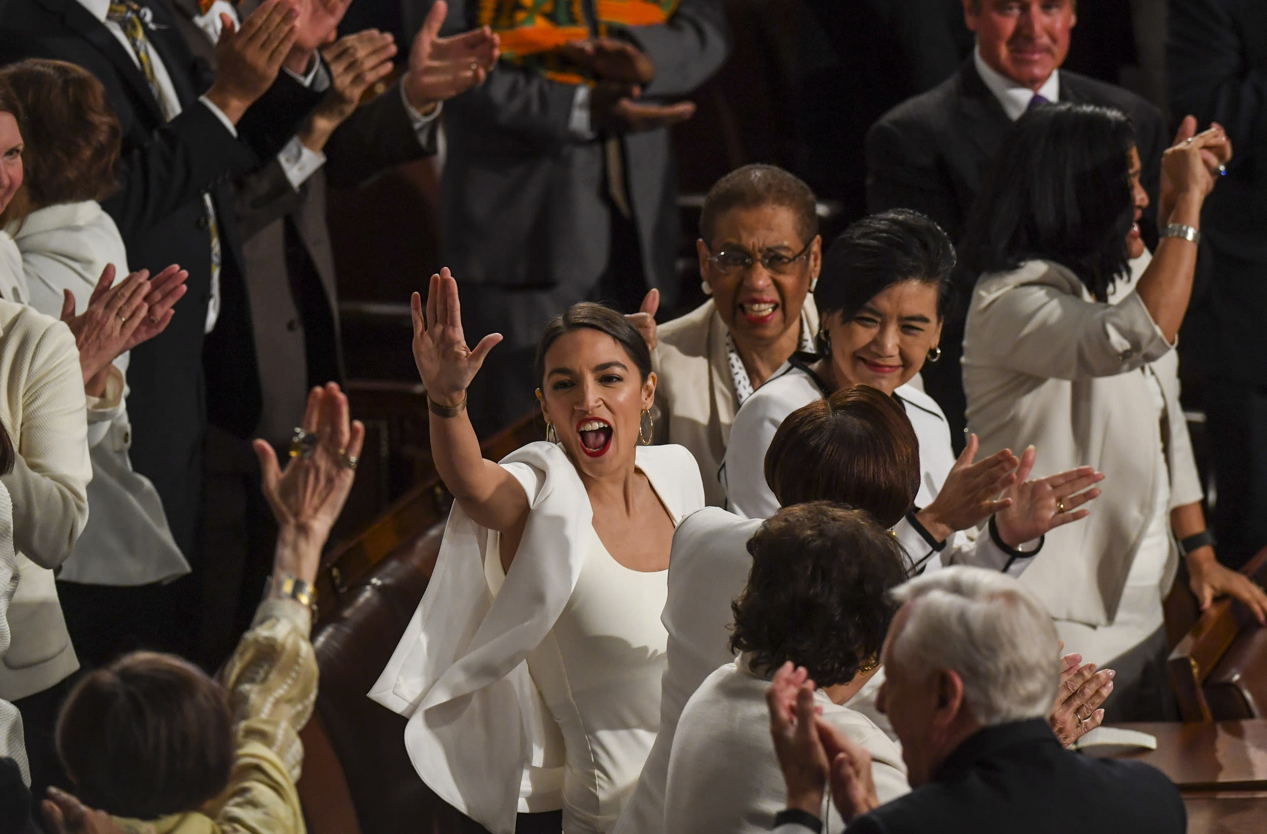 WASHINGTON, DC - FEBRUARY 05: Rep. Alexandria Ocasio-Cortez (D-N.Y.) high-fives other congresswomen after President Donald J. Trump acknowledged newly elected female members of congress during the State of the Union address before members of Congress in the House chamber of the U.S. Capitol February 5, 2019 in Washington, DC.  (Photo by Toni L. Sandys/The Washington Post via Getty Images)