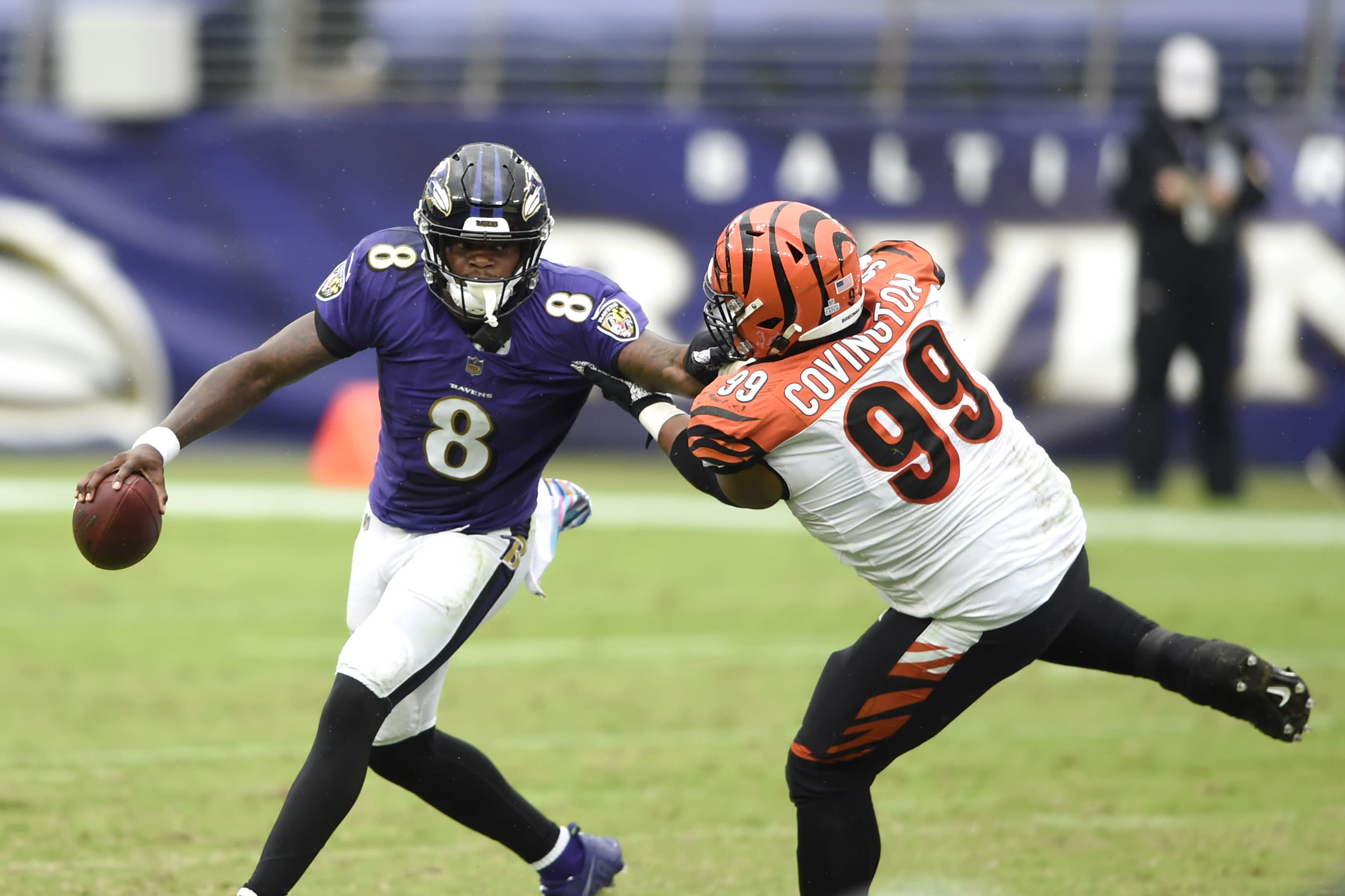 Baltimore Ravens quarterback Lamar Jackson (8) tries to avoid a sack by Cincinnati Bengals defensive tackle Christian Covington (99) during the second half of an NFL football game, Sunday, Oct. 11, 2020, in Baltimore. (AP Photo/Gail Burton)
