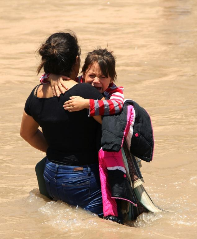 A Central American migrant and a girl cross the Rio Grande to claim asylum on the US side in June 2019 (AFP Photo/HERIKA MARTINEZ)