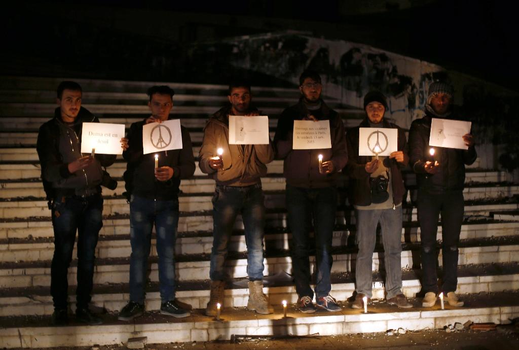"""Syrians in a rebel stronghold east of Damascus stand vigil for Parisians on November 14, 2015, as 49 armed factions in the Syrian conflict joined to condemn the November 13 attacks """"in the strongest terms"""" as """"against (Islamic) laws and human values"""""""