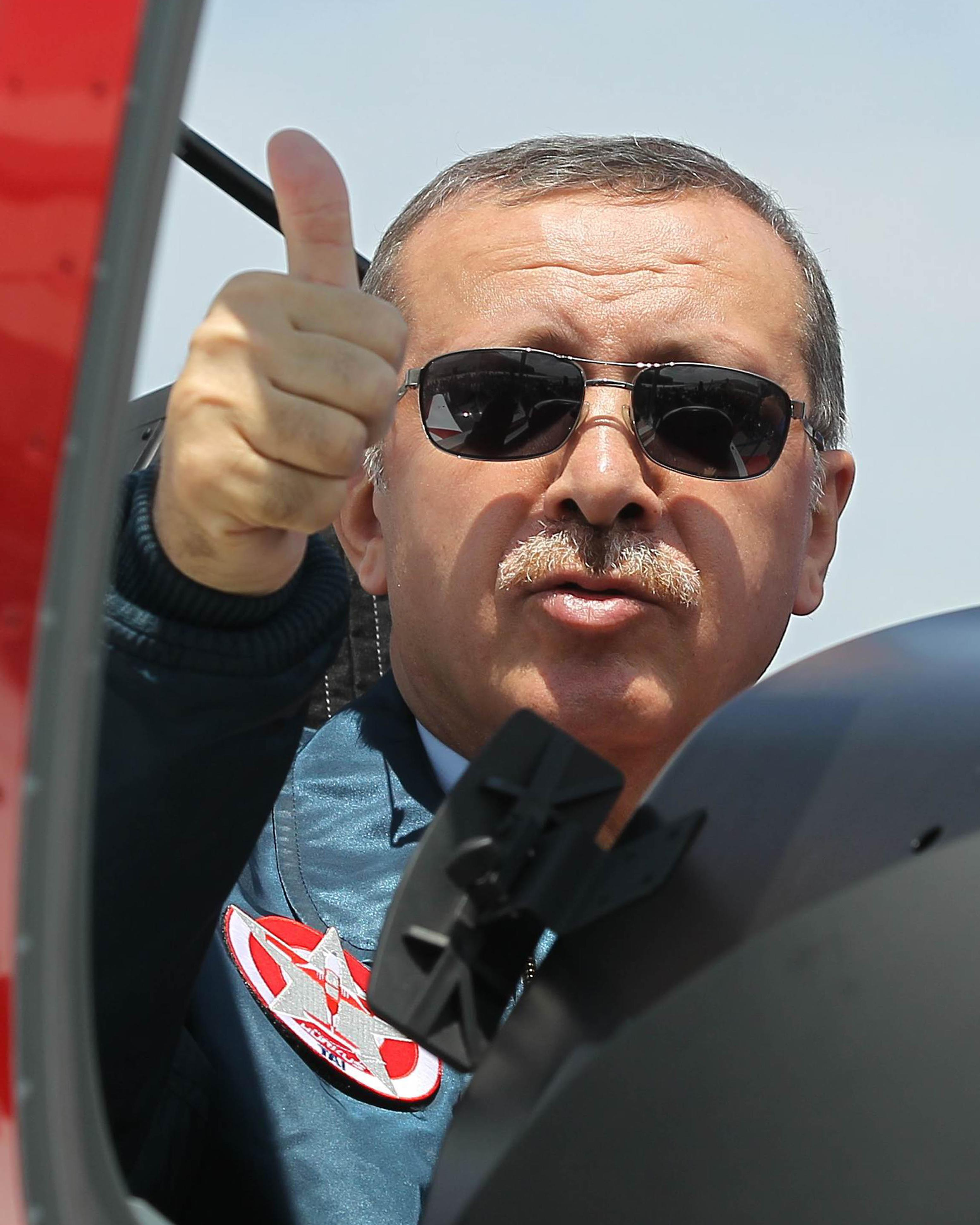 "Turkish Prime Minister Recep Tayyip Erdogan gestures while sitting in the cockpit of Hurkus (Freebird), Turkey's first locally produced military training plane, a two-seat turboprop plane, unveiled during a ceremony outside Ankara, Turkey, Wednesday, June 27, 2012. Erdogan kept up his pressure on Syria on Wednesday, saying ""we would never hesitate to respond with all our power to hostile acts, attacks and threats against us."" (AP Photo)"
