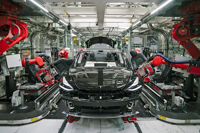 A photograph of the front of a Tesla car while it's being assembled by robots on the assembly line.