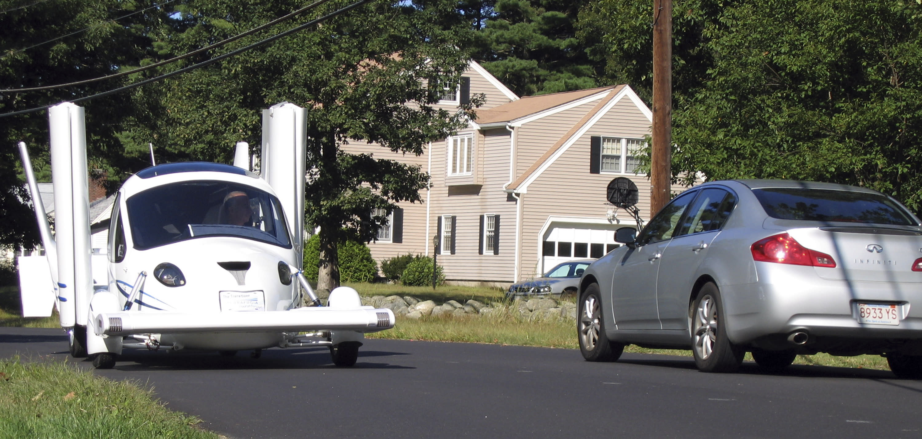 In this 2008 photo, the Terrafugia Transition drives down a street during road testing in Westford, Mass. The Terrafugia can take off and cruise at 115 mph, land, fold up it wings in 30 seconds and turn back into a car. In two years you'll be able to get one for $194,000, according to the Paxton, Ill., man who helped create it. (AP Photo/courtesy Terrafugia)