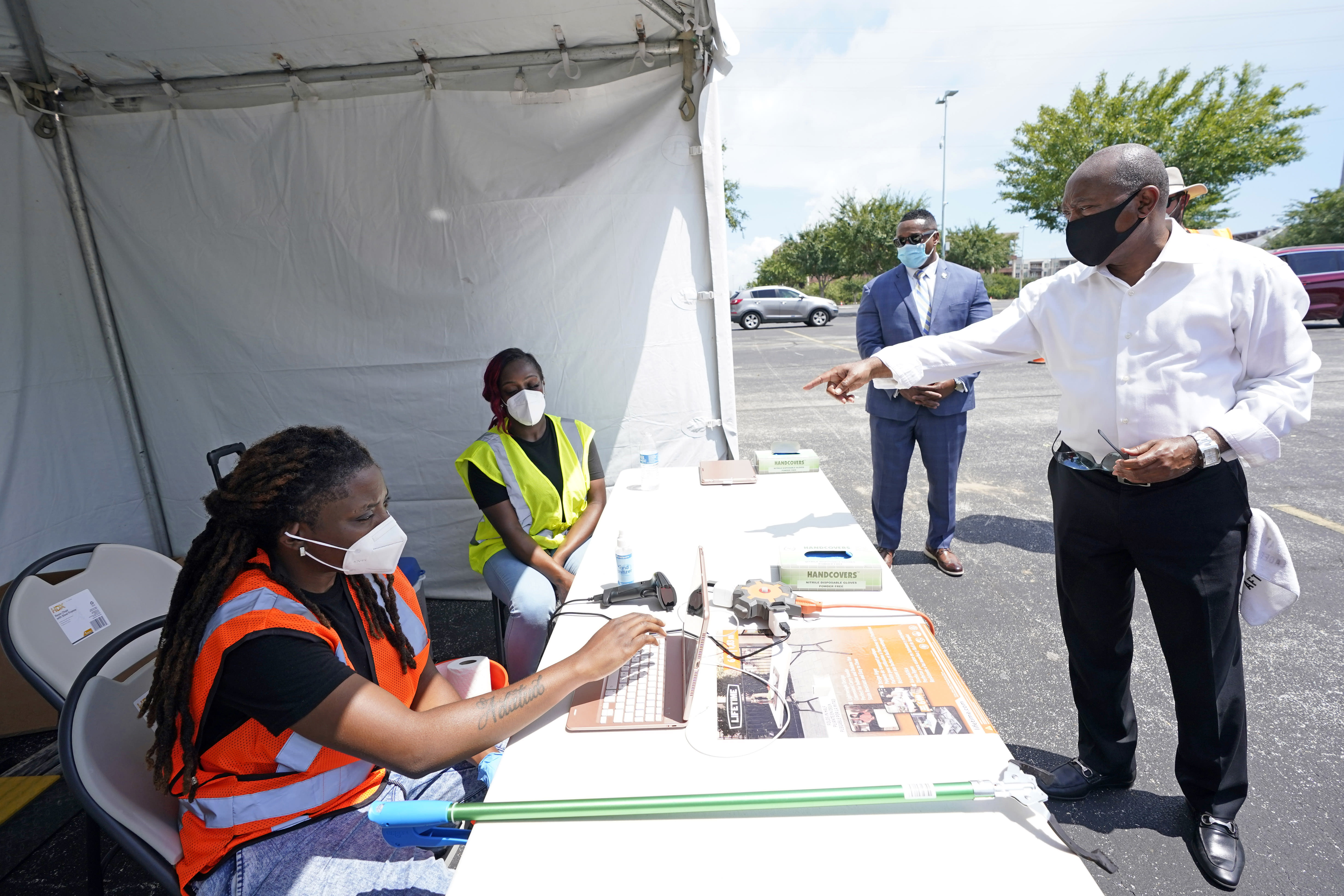 Houston Mayor Sylvester Turner, right, talks with healthcare workers at a Texas Division of Emergency Management free COVID-19 testing site at Minute Maid Park Saturday, Aug. 8, 2020, in Houston. UNICEF-USA is teaming up with Turner for the organization's first-ever initiative to support kids in the U.S. (AP Photo/David J. Phillip)