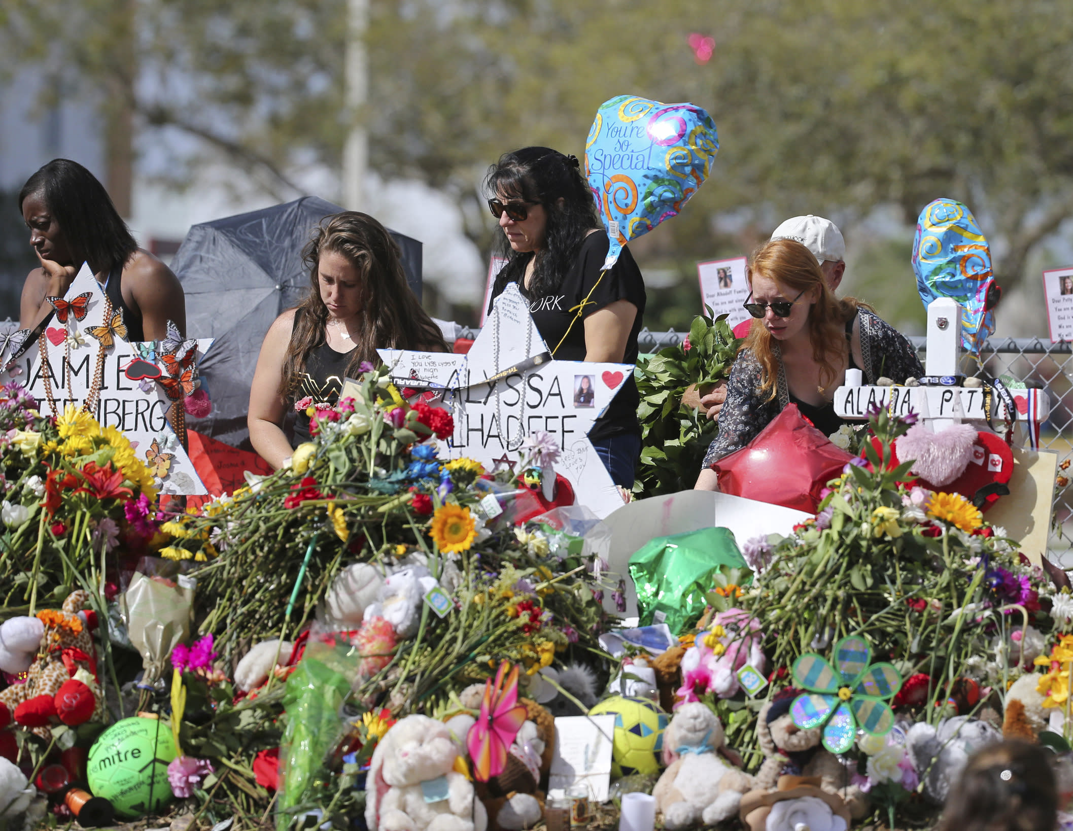 FILE - In this Feb. 25, 2018 file photo, mourners bring flowers as they pay tribute at a memorial for the victims of the shooting at Marjory Stoneman Douglas High School, in Parkland, Fla. The community of Parkland, Florida, is focusing on suicide prevention programs after two survivors of the Florida high school massacre there killed themselves this month. Parkland Mayor Christine Hunschofsky said Monday, March 25, 2019, that officials are publicizing the available counseling services after a second Marjory Stoneman Douglas High School student apparently killed himself over the weekend. (David Santiago/Miami Herald via AP, File)