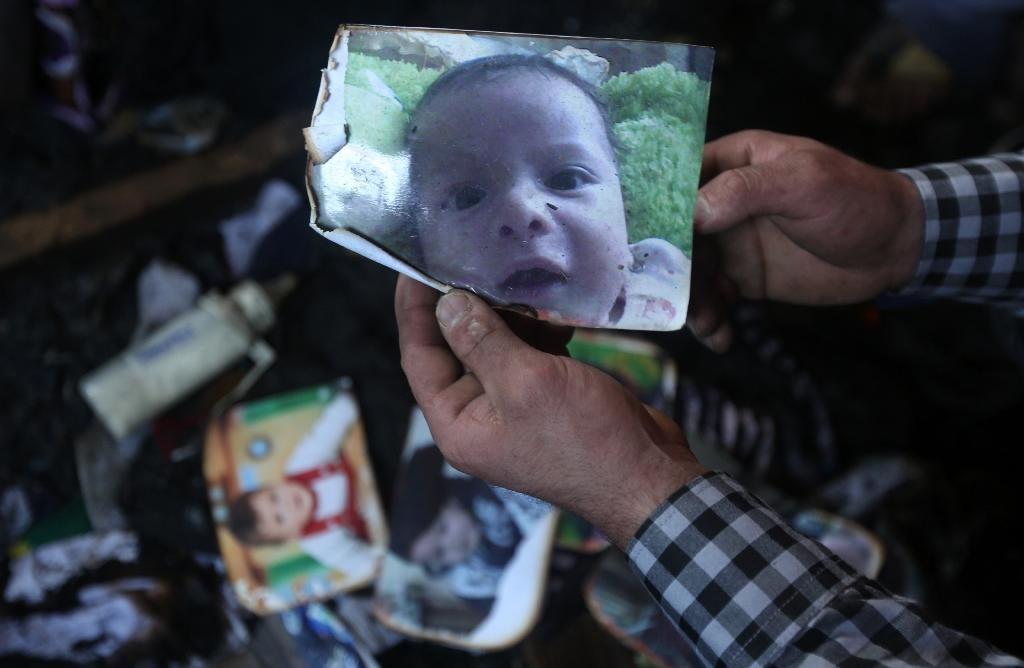 A picture taken on July 31, 2015 shows a man holding a picture of 18-month-old Palestinian toddler Ali Saad Dawabsha, who died when his family house was set on fire by Jewish settlers in the West Bank village of Duma (AFP Photo/Jaafar Ashtiyeh)
