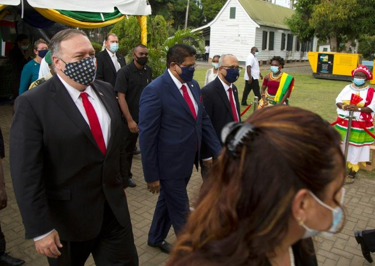 US Secretary of State Mike Pompeo (left) walks past ceremonial drummers following a news conference at Suriname's presidential palace