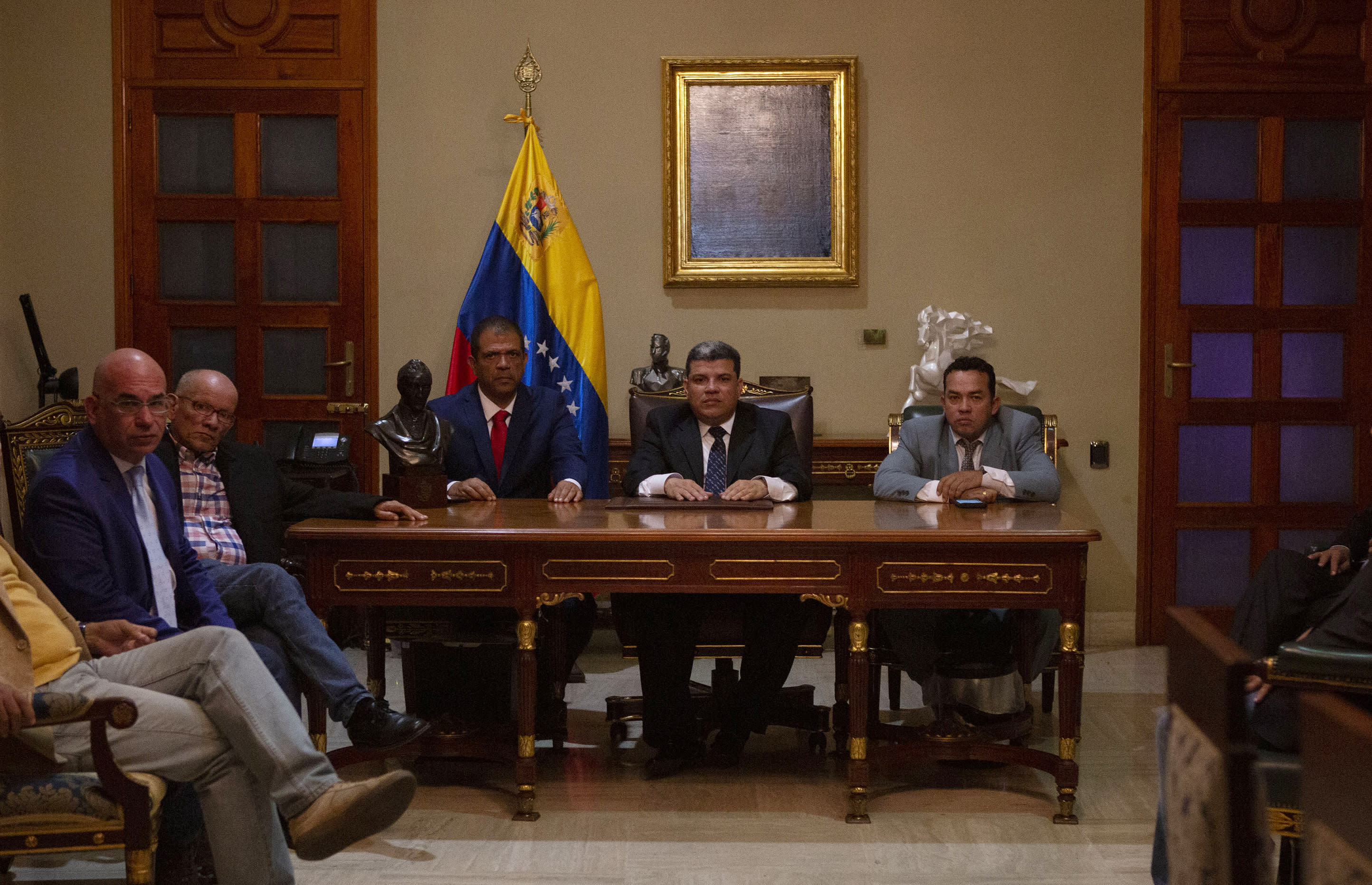Lawmaker Luis Parra, center, sits with fellow lawmakers Franklyn Duarte, right, and Jose Noriega after they were sworn-in as president, first vice president, and second vice president of the legislature, as they pose for a photo inside the presidential office of the National Assembly in Caracas, Venezuela, Sunday, Jan. 5, 2020. Venezuelan opposition leader Juan Guaidó was violently blocked from presiding over the special session of congress where Parra, Duarte and Noriega tried to install a substitute in what was condemned as a hijacking of the country's last democratic institution. (AP Photo/Andrea Hernandez Briceño)