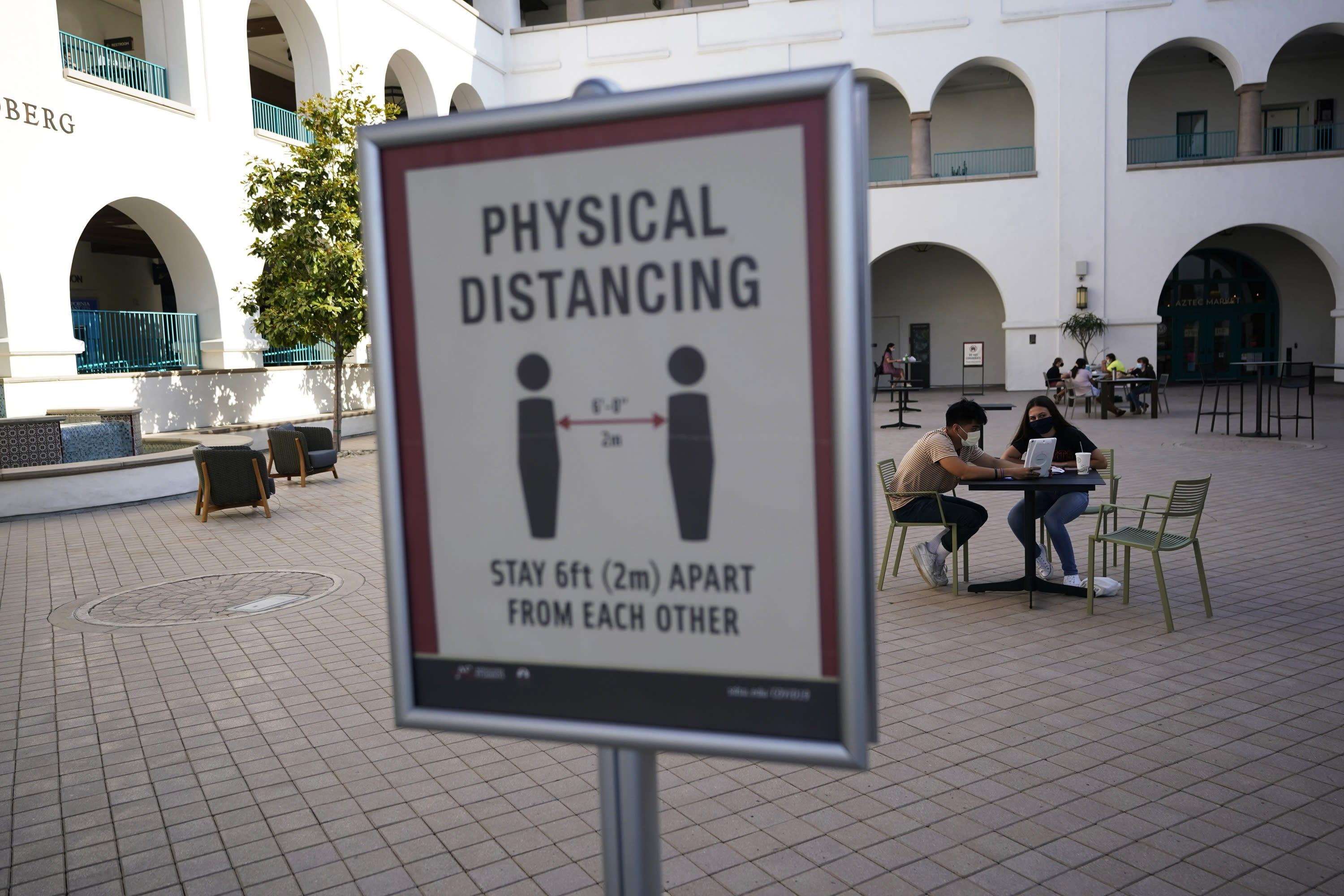FILE - In this Wednesday, Sept. 2, 2020, file photo, people sit at tables at San Diego State University in San Diego. A coronavirus outbreak of more than 700 cases reported at San Diego State University has put all of San Diego County, with more than 3 million people, at risk of having to close indoor dining and shopping, many for a third time under California guidelines. (AP Photo/Gregory Bull, File)