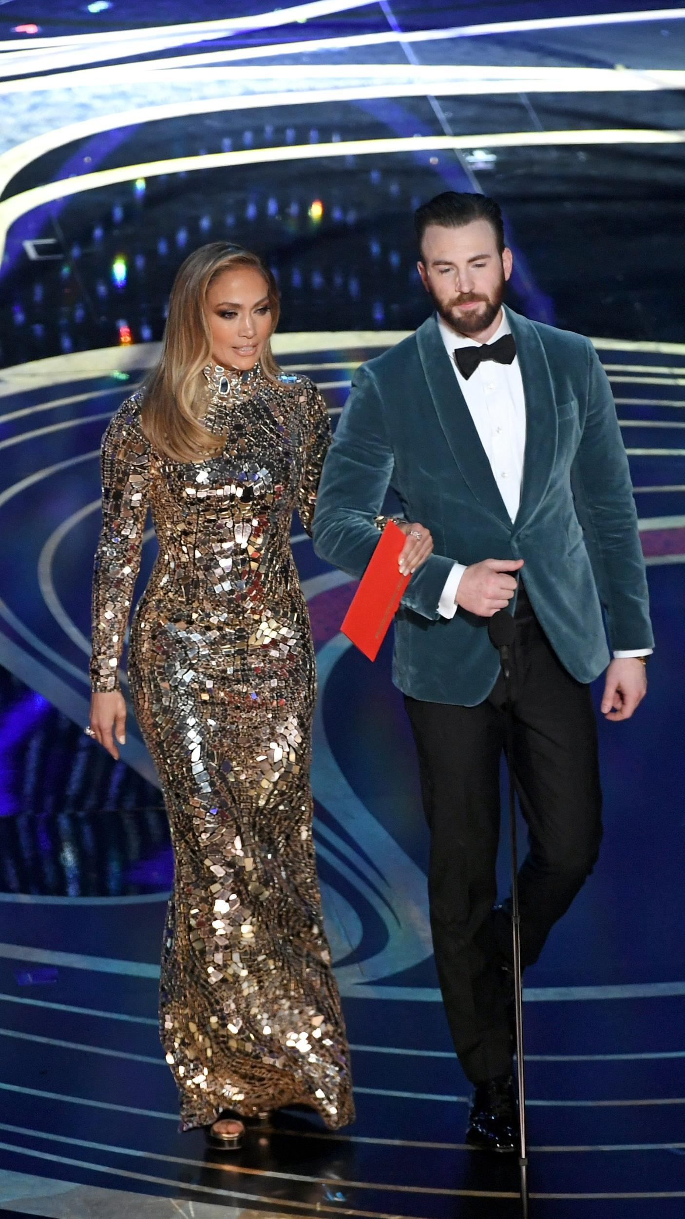 HOLLYWOOD, CALIFORNIA - FEBRUARY 24: (EDITORS NOTE: Retransmission with alternate crop.) (L-R) Jennifer Lopez and Chris Evans speak onstage during the 91st Annual Academy Awards at Dolby Theatre on February 24, 2019 in Hollywood, California. (Photo by Kevin Winter/Getty Images)