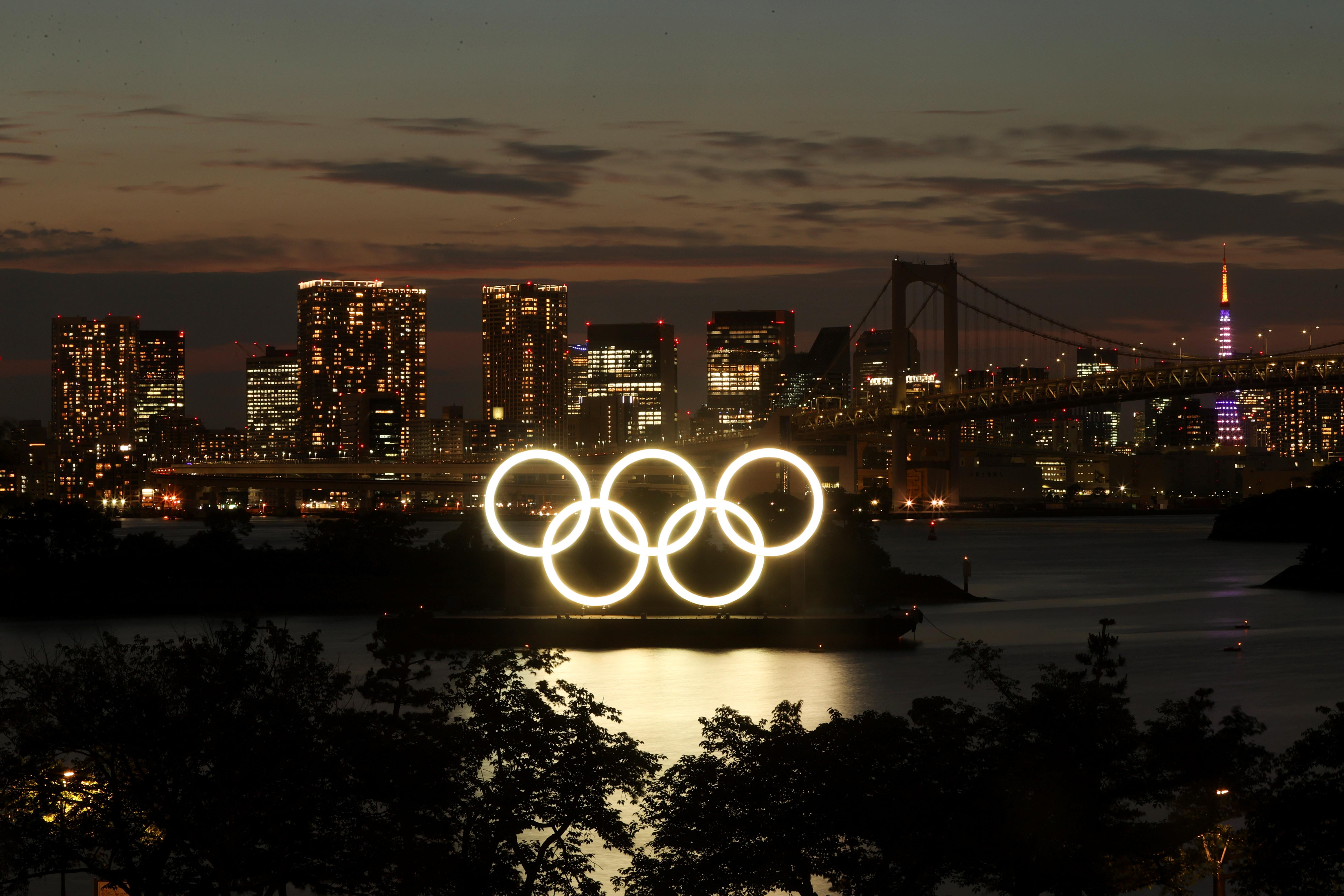 A general view of the Olympic Rings installed on a floating platform with the Rainbow Bridge in the background in preparation for the Tokyo 2020 Olympic Games in Tokyo, Japan June 21, 2021. Picture taken with long exposure.  REUTERS/Pawel Kopczynski