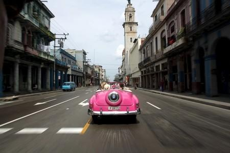 Tourists ride in a vintage car in Havana