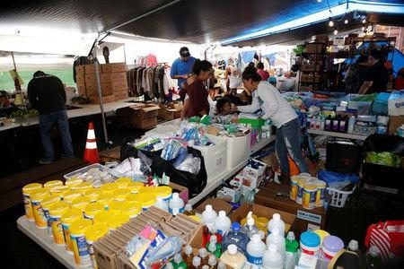Mehana Kihoi hands out goods to Leilani Estate evacuees at the community organized Pu'uhonua o Puna, a center to help those affected by the recent lava eruption, in Pahoa, Hawaii, U.S., May 29, 2018. REUTERS/Marco Garcia