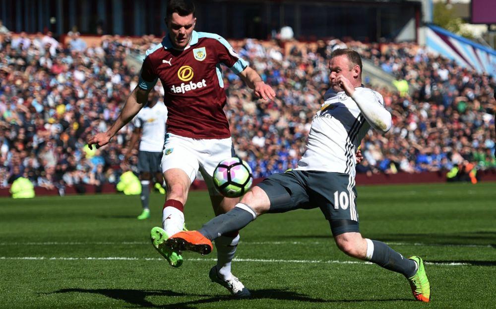 Michael Keane (left) in action against Wayne Rooney - AFP