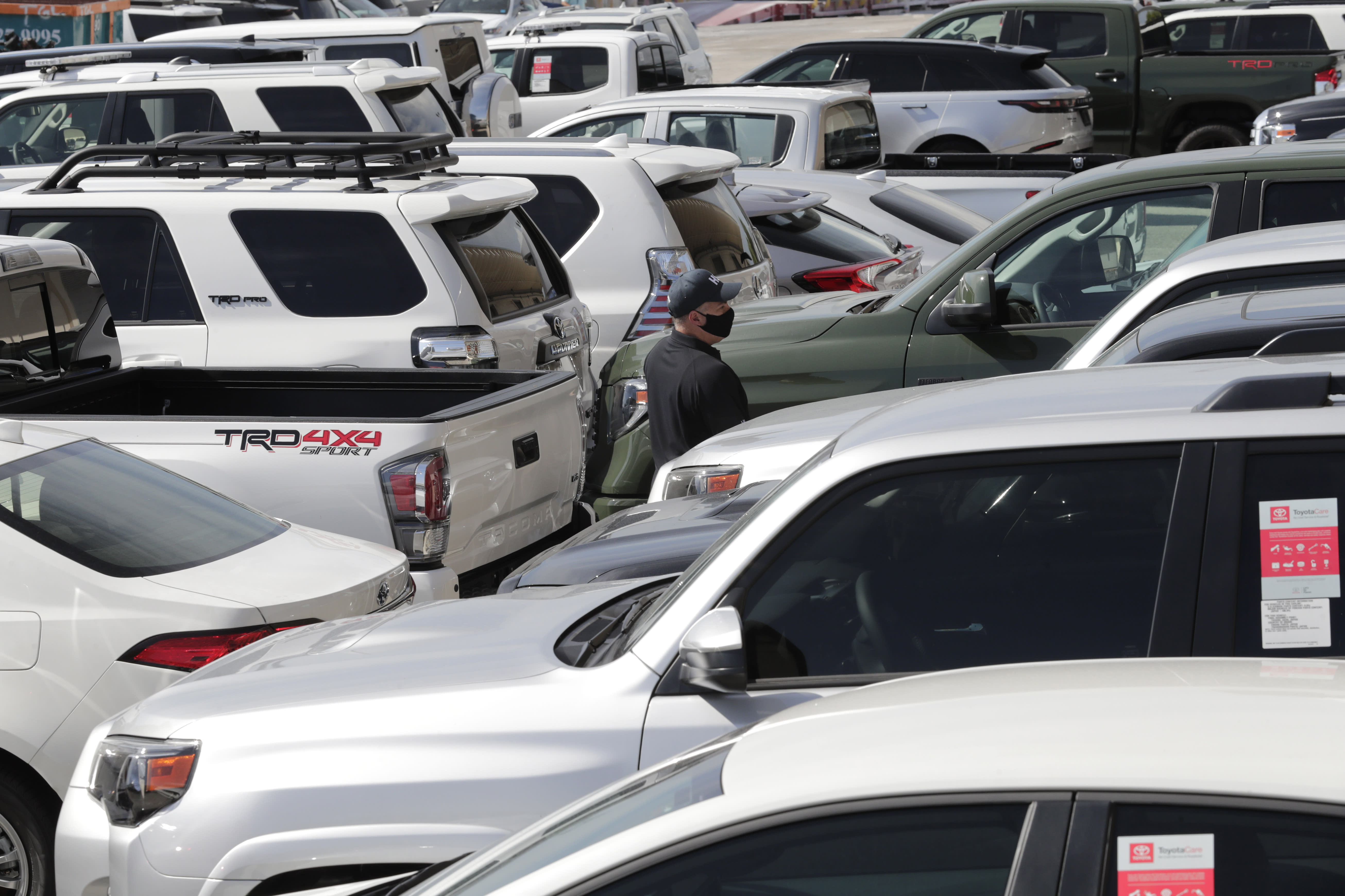 An official with Homeland Security Investigations walks among vehicles worth an estimated $3.2 million, at Port Everglades after they were seized by Homeland Security Investigations, Wednesday, July 8, 2020, in Fort Lauderdale, Fla. The vehicles were to be smuggled to Venezuela in violation of U.S. export laws and sanctions against the socialist Venezuelan government. (AP Photo/Lynne Sladky)