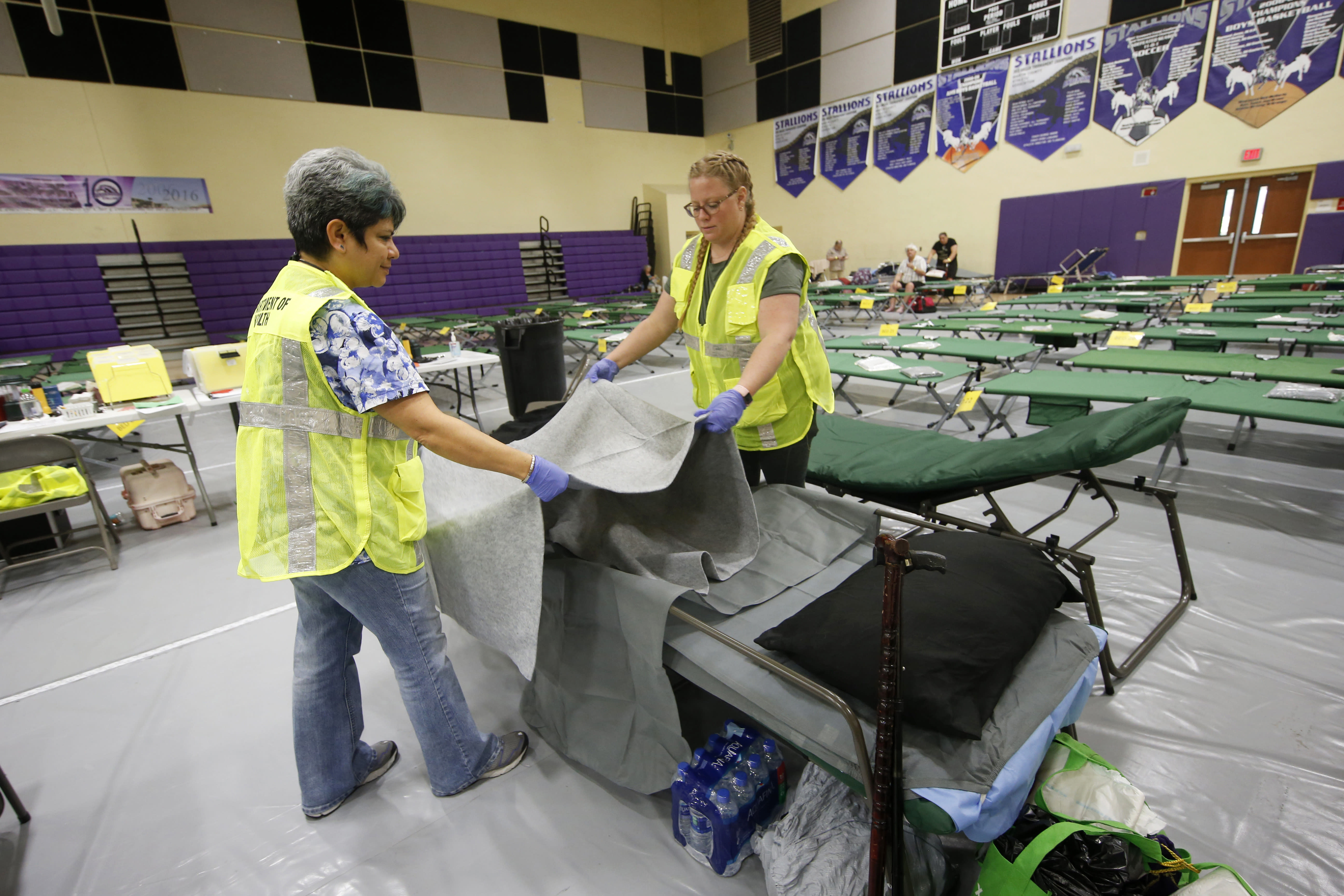 Florida Department of Health staffers set up beds at an evacuation shelter for people with special needs in preparation for Hurricane Dorian at Dr. David L. Anderson Middle School in Stuart Fla. Sunday Sept. 1 2019. Some coastal areas are under a
