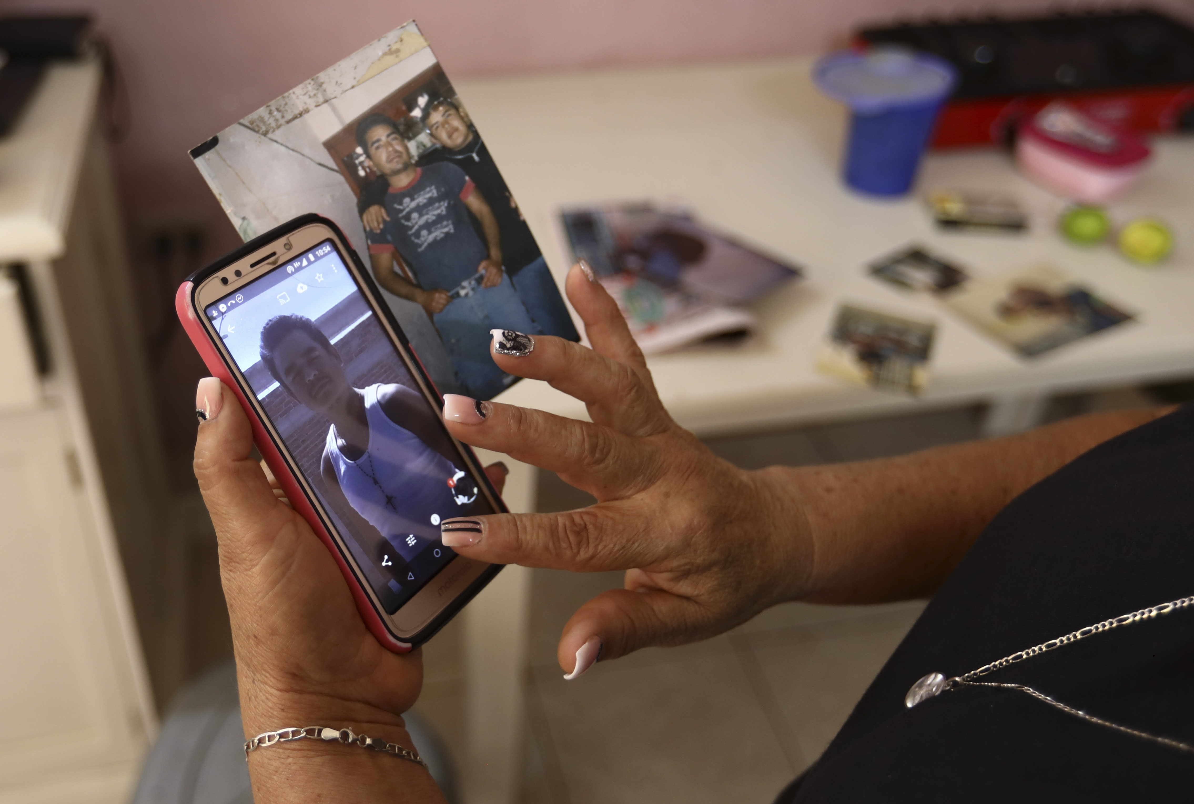 Rosa Alba Santoyo shows photos of two of her three adult children who died during an attack on a drug rehabilitation center where they were being treated, at her home in Irapuato, Mexico, Thursday, July 2, 2020. Gunmen burst into the drug rehabilitation center and opened fire Wednesday, killing 24 people and wounding seven, authorities said. (AP Photo/Eduardo Verdugo)