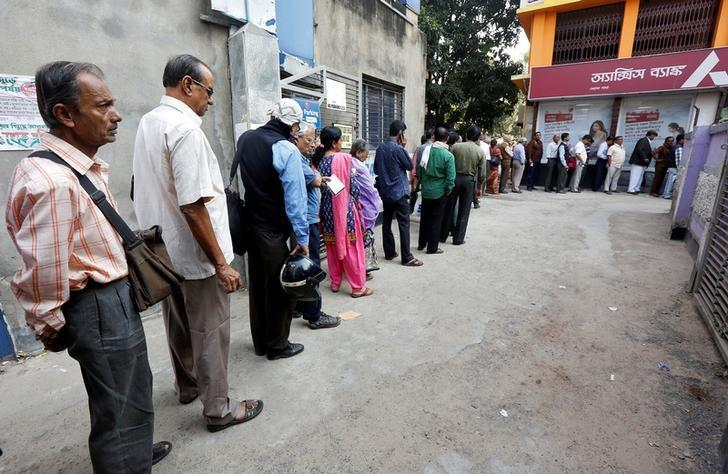 People queue outside a bank to withdraw cash and deposit their old high denomination banknotes in Kolkata