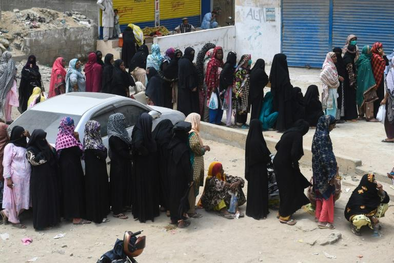 Women in Karachi stand in line on April 13, 2020 to collect cash through a bank under an emergency government program for needy families amid restrictions imposed over the coronavirus pandemic