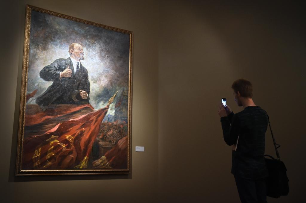 "A man takes a picture of Soviet artist Aleksandr Gerasimov's painting ""Lenin on the Tribune"" at the Manezh Central Exhibition Hall in Moscow on November 10, 2015 (AFP Photo/Alexander Nemenov)"