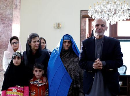 "Afghanistan's President Ashraf Ghani (R) speaks to the media after Sharbat Gula (2nd R), the green-eyed ""Afghan Girl"" whose 1985 photo in National Geographic became a symbol of her country's wars, arrived in Kabul, Afghanistan November 9, 2016. REUTERS/Mohammad Ismail"