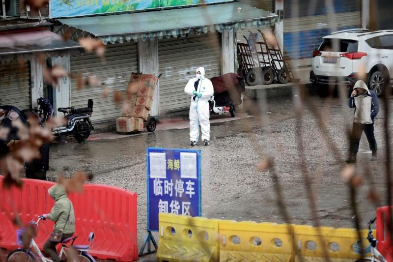 A worker in a protective suit is seen at the closed seafood market in Wuhan