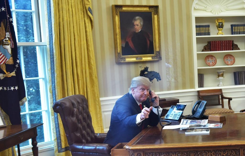 US President Donald Trump(L)seen through an Oval Office window, speaks on the phone to King Salman of Saudi Arabia in the Oval Office of the White House on January 29, 2017 in Washington, DC (AFP Photo/Mandel Ngan)