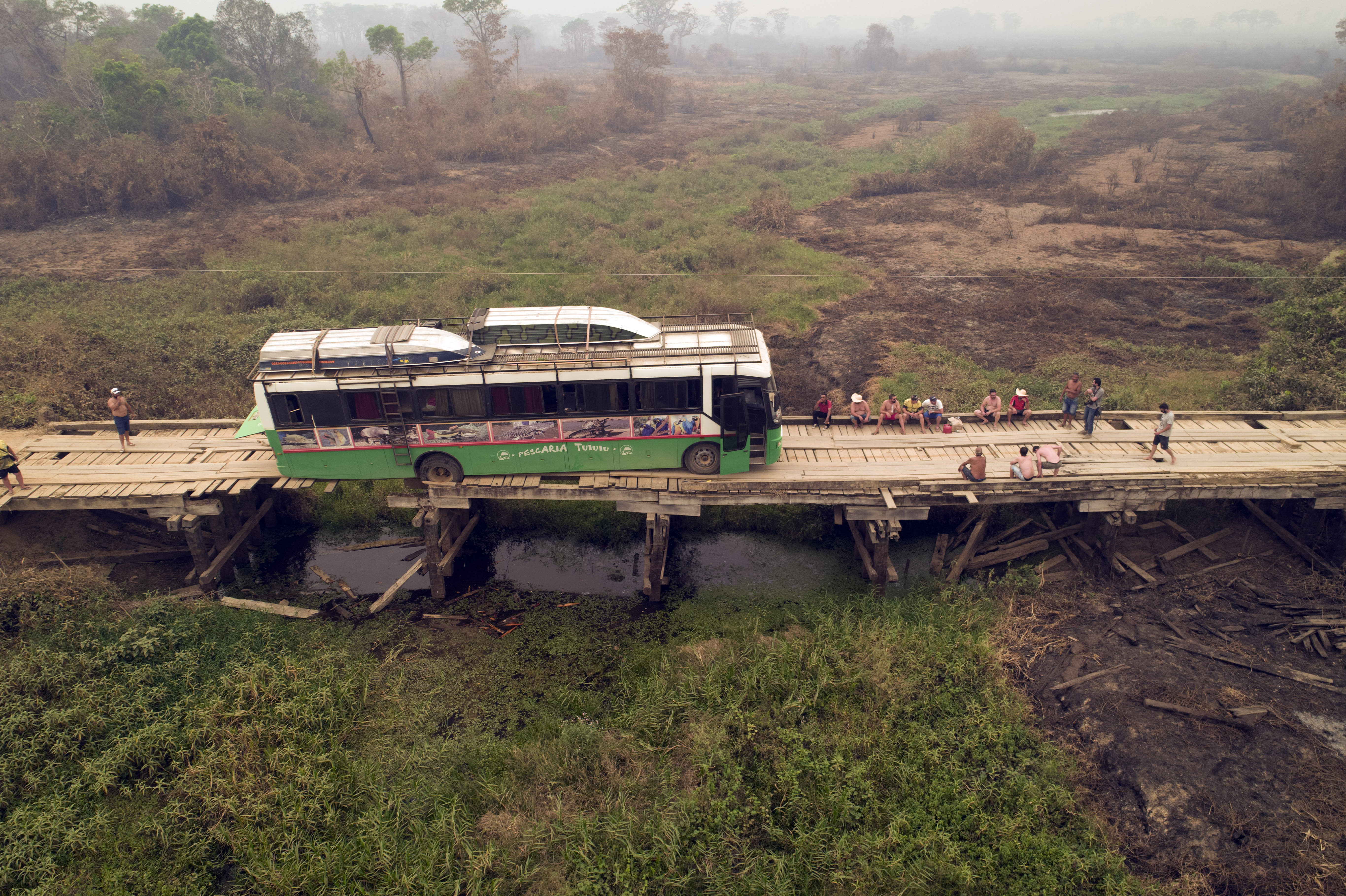 Tourists sit on a bridge railing after their sports fishing tour bus became stuck on a bridge damaged by wildfires, on the Trans-Pantanal highway in the Pantanal wetlands near Pocone, Mato Grosso state, Brazil, Friday, Sept. 11, 2020. Both sides of the highway usually feature pools of water, even in its dry season. (AP Photo/Andre Penner)