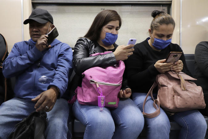 17 April 2020, Mexico, Mexiko-Stadt: People, sometimes wearing face masks, make phone calls or look at information on their mobile phones while riding the subway in the middle of the Corona pandemic. From 17.04.2020, the wearing of face masks will be compulsory in the subway. The number of Covid-19 infected people in Mexico has risen to 6297. Photo: Gerardo Vieyra/dpa (Photo by Gerardo Vieyra/picture alliance via Getty Images)