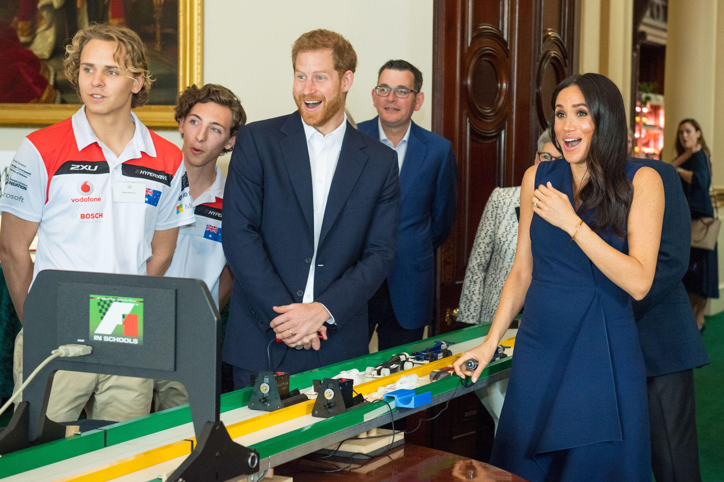 The Duke and Duchess of Sussex react after starting model Formula 1 cars at a demonstration by Formula 1 in Schools, at a reception given by the Governor of Victoria, at Government House during their visit to Melbourne, on the third day of the royal couple's visit to Australia.