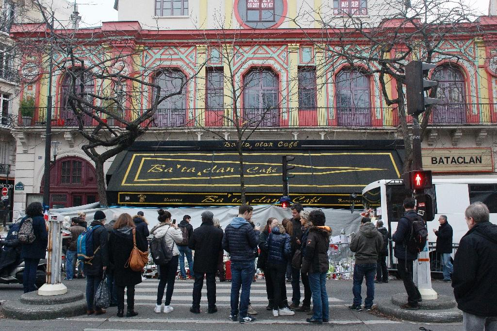 People pay tribute to victims in front of the music hall Bataclan in Paris on December 13, 2015, a month after the Paris terror attacks