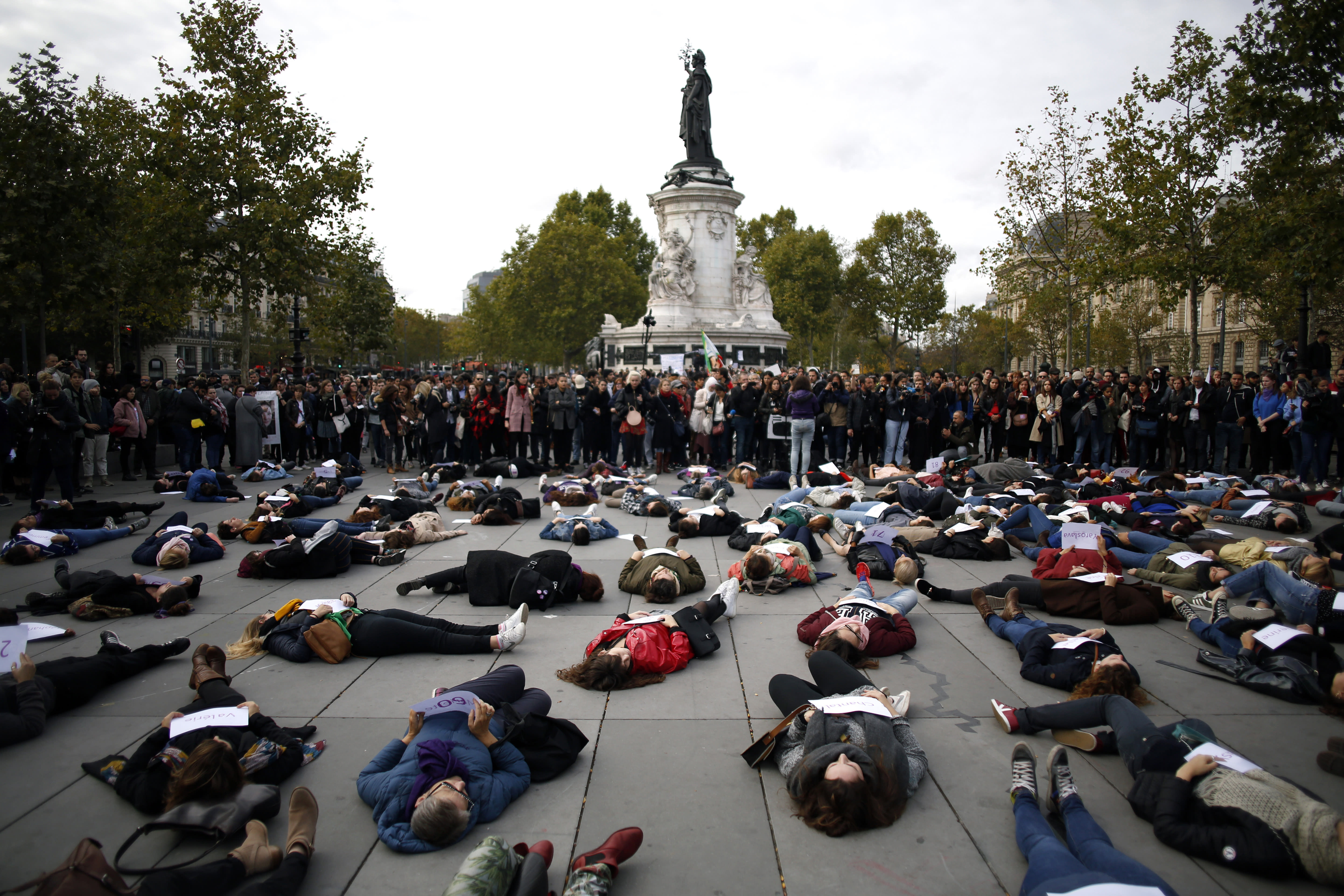 FILE - In this Oct.19, 2019 file photo, women stage a die-in while holding placards with the names of women killed by their partners, during a protest, in Paris. A French government commission examining domestic violence is recommending that authorities now confiscate firearms from individuals following the first complaint of family violence levied against them. In France, a woman is killed by her partner every three days, according to government statistics. (AP Photo/Thibault Camus, File)